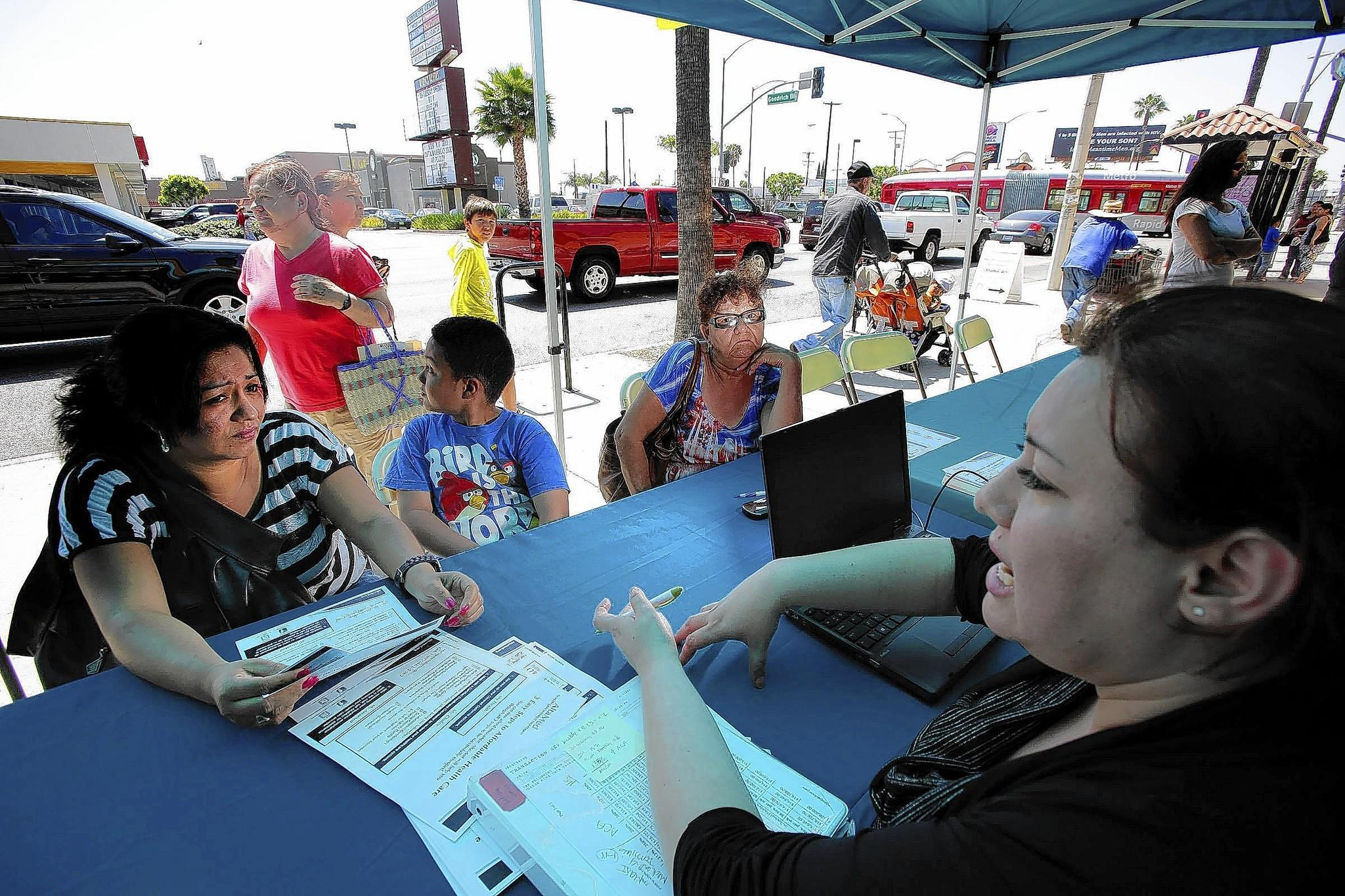 As of Thursday, Covered California said 70,000 people had finished enrolling since March 31 and overall it expects to exceed 1.3 million health plan customers. Above, a family in the City of Commerce gets information about Obamacare on Tuesday.