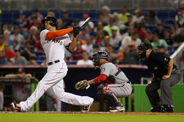 Giancarlo Stanton of the Miami Marlins hits a three run home run during a game against the Washington Nationals at Marlins Park on April 15, 2014 in Miami, Florida. All uniformed team members are wearing jersey number 42 in honor of Jackie Robinson Day