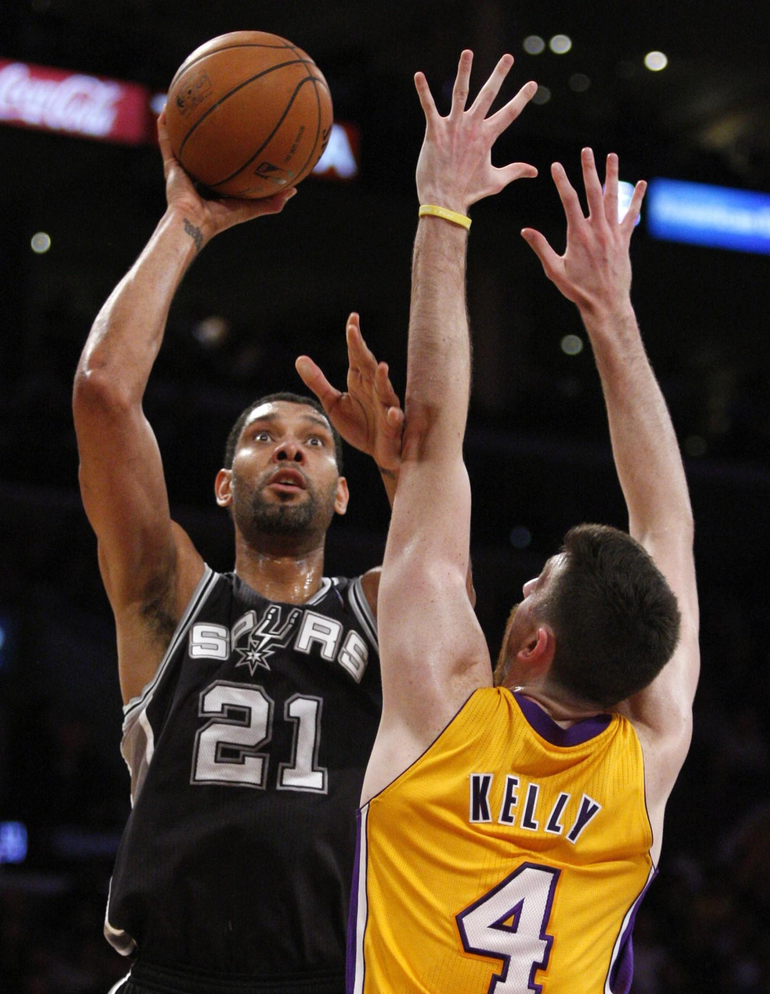 Lakers forward Ryan Kelly stands his ground as Spurs power forward Tim Duncan looks to shoot.