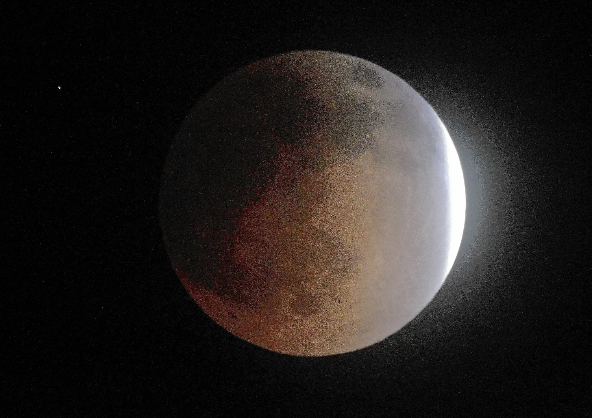 "A sliver of the moon remains outside Earth's shadow during Tuesday's lunar eclipse. The moon took on a reddish glow during the event known as a ""blood moon."""
