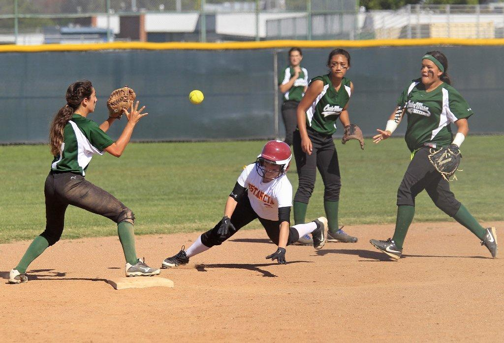 Estancia High's Bree Vernon, bottom center, is safe at second base after Costa Mesa's Anessa Farldow, far right, miss throws the ball to teammate Brenna Alvis, far left, in an Orange Coast League game on Tuesday.