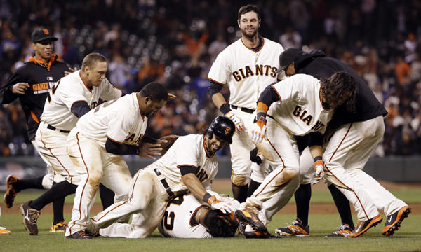 San Francisco Giants catcher Hector Sanchez, bottom center, is mobbed by his teammates after driving in the winning run in the bottom of the 12th inning of the Dodgers' 3-2 loss.