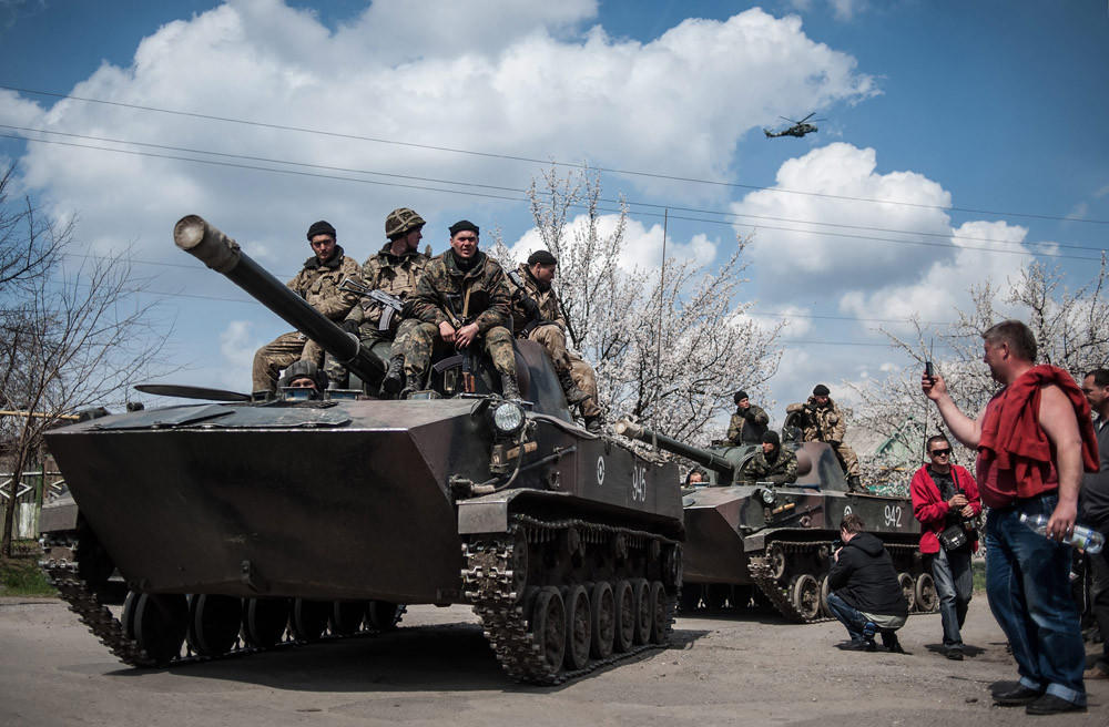 Pro-Russian protesters take photos of Ukrainian soldiers sitting on their armored vehicle in Kramatorsk, Ukraine, on April 16.