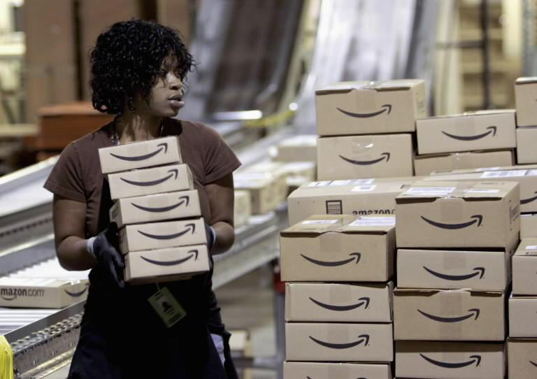 A worker loads a shipment of outgoing boxes at the Amazon.com warehouse facility in New Castle, Del.