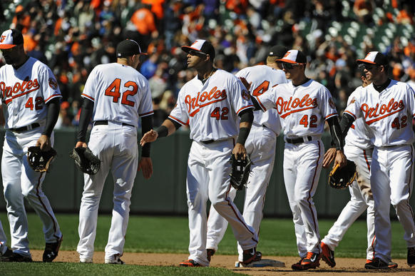 Orioles players, all wearing No. 42 in honor of Jackie Robinson, celebrate after the club's 3-0 win over the Tampa Bay Rays at Camden Yards.