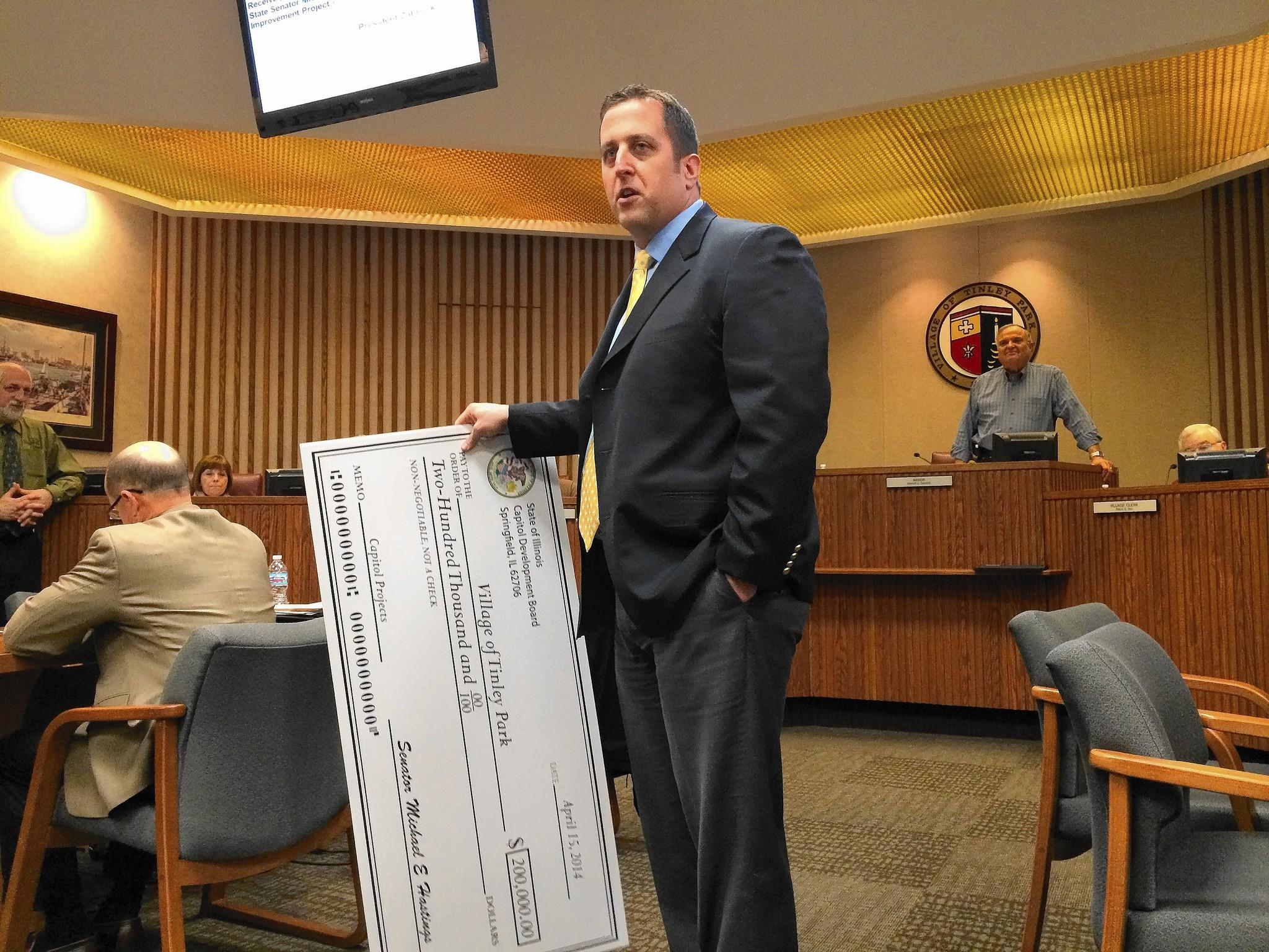 State Sen. Michael Hastings presents Tinley Park officials with a $200,000 check for a new traffic signal near the 80th Avenue train station.