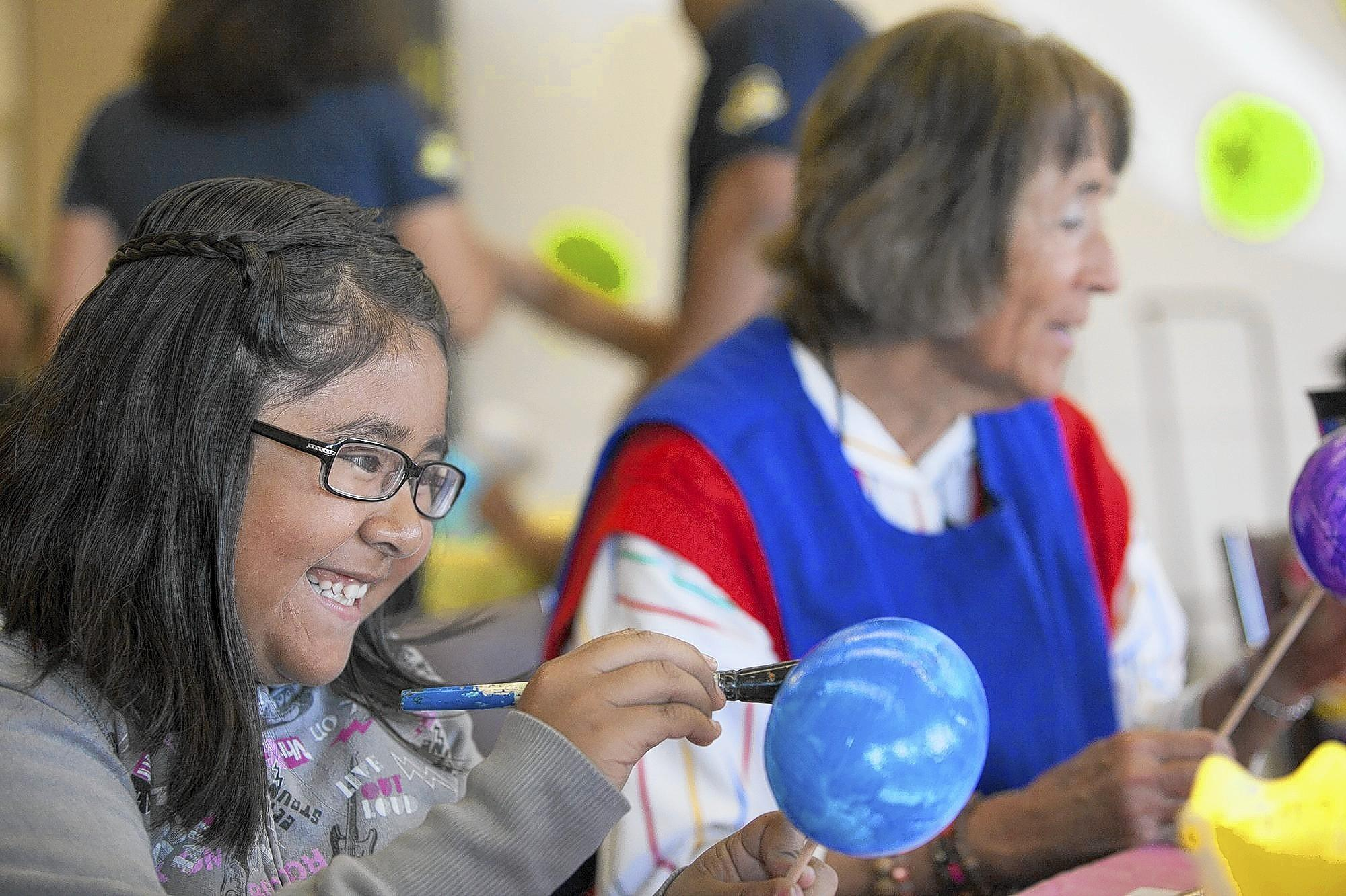 Maricruz Torres, 9, a student from Oak View Elementary school paints Easter eggs with seniors at the Rodgers Senior Center on Monday.