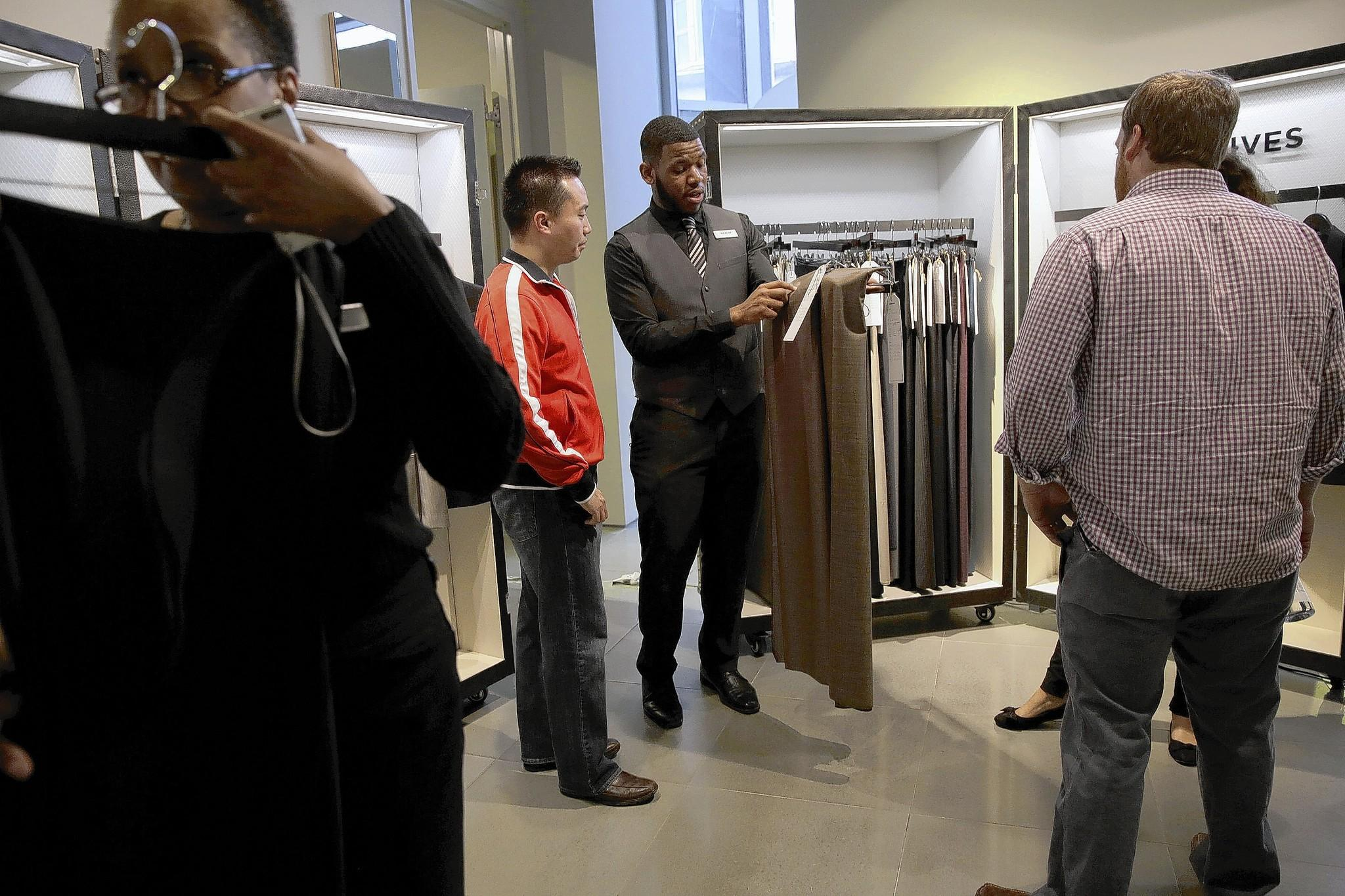 Style guide Marlin Ross II walks customer Jason Chan through suit fabric choices and upgrades at the Indochino Traveling Tailor pop-up store at Block 37 on State Street in Chicago. A growing number of online retailers are investing in bricks-and-mortar shops to put in valuable face time with their customers.