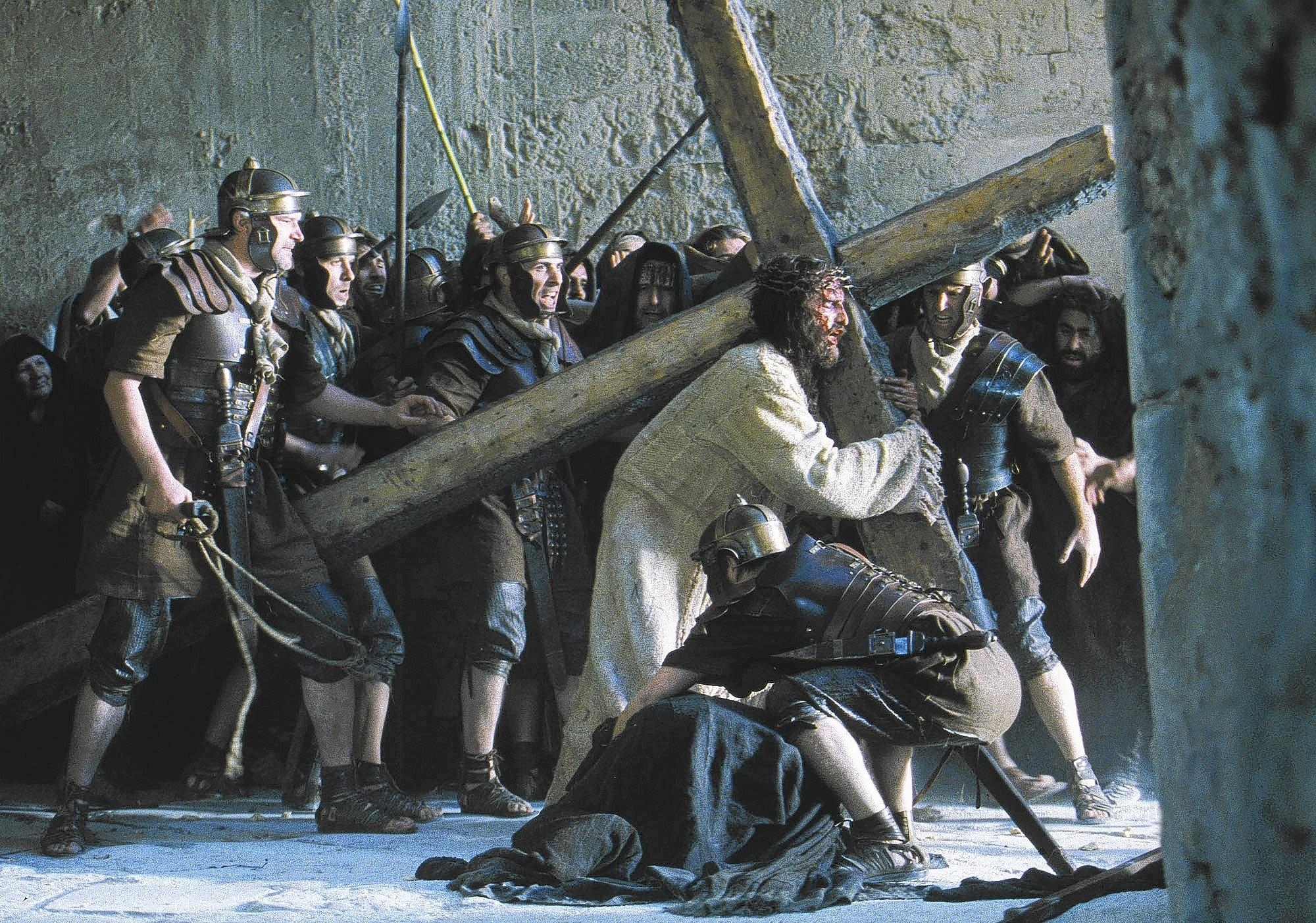Surrounded by onlookers and Roman troops, Jesus, portrayed by the actor John Caviezel, wears a crown of thorns as he carries a wooden cross to the site of his Crucifixion in Mel Gibson's new film 'The Passion of The Christ,' which recounts the last 12 hours of Jesus' life.