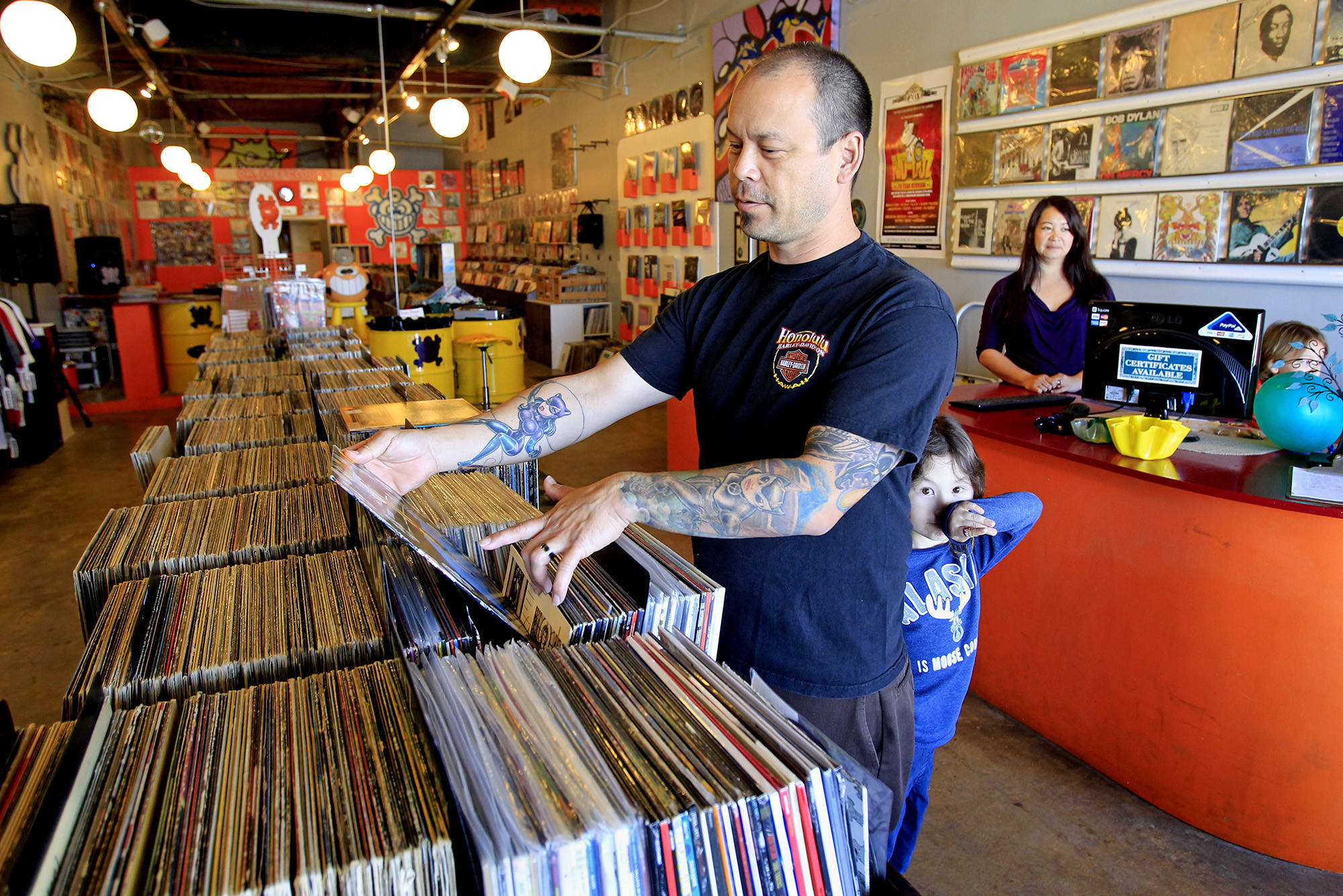 Steven DeZwart, 45, of Garden Grove looks through vinyl records accompanied by his son Andy, 5, bottom center, at Dr. Freecloud's Record Shoppe in Fountain Valley on Tuesday.