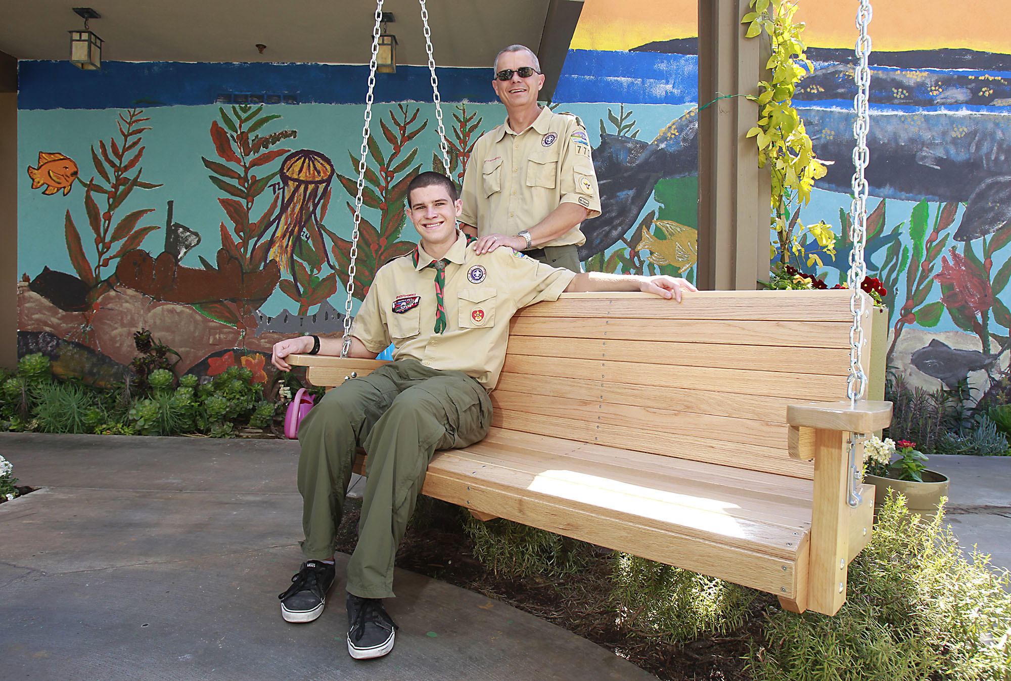 David Bailey of troop 773 in Laguna Niguel, sits on the wooden bench he built for his Eagle Scout project for the Glennwood House. He built the bench with help from his dad.