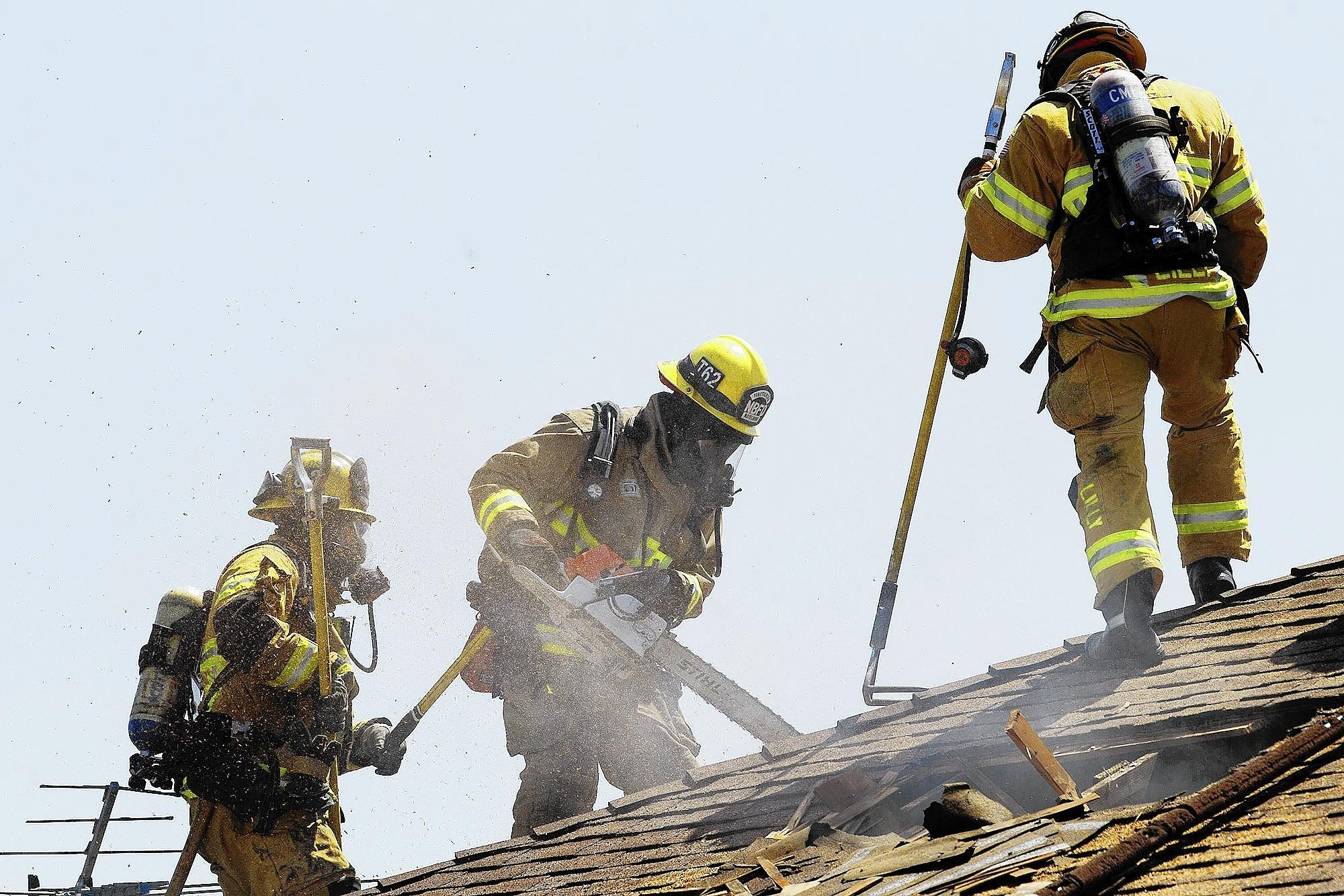 Newport Beach and Costa Mesa Fire Department personnel vent the roof of a house that caught fire in the 200 block of Sherwood Street in Costa Mesa on Wednesday.