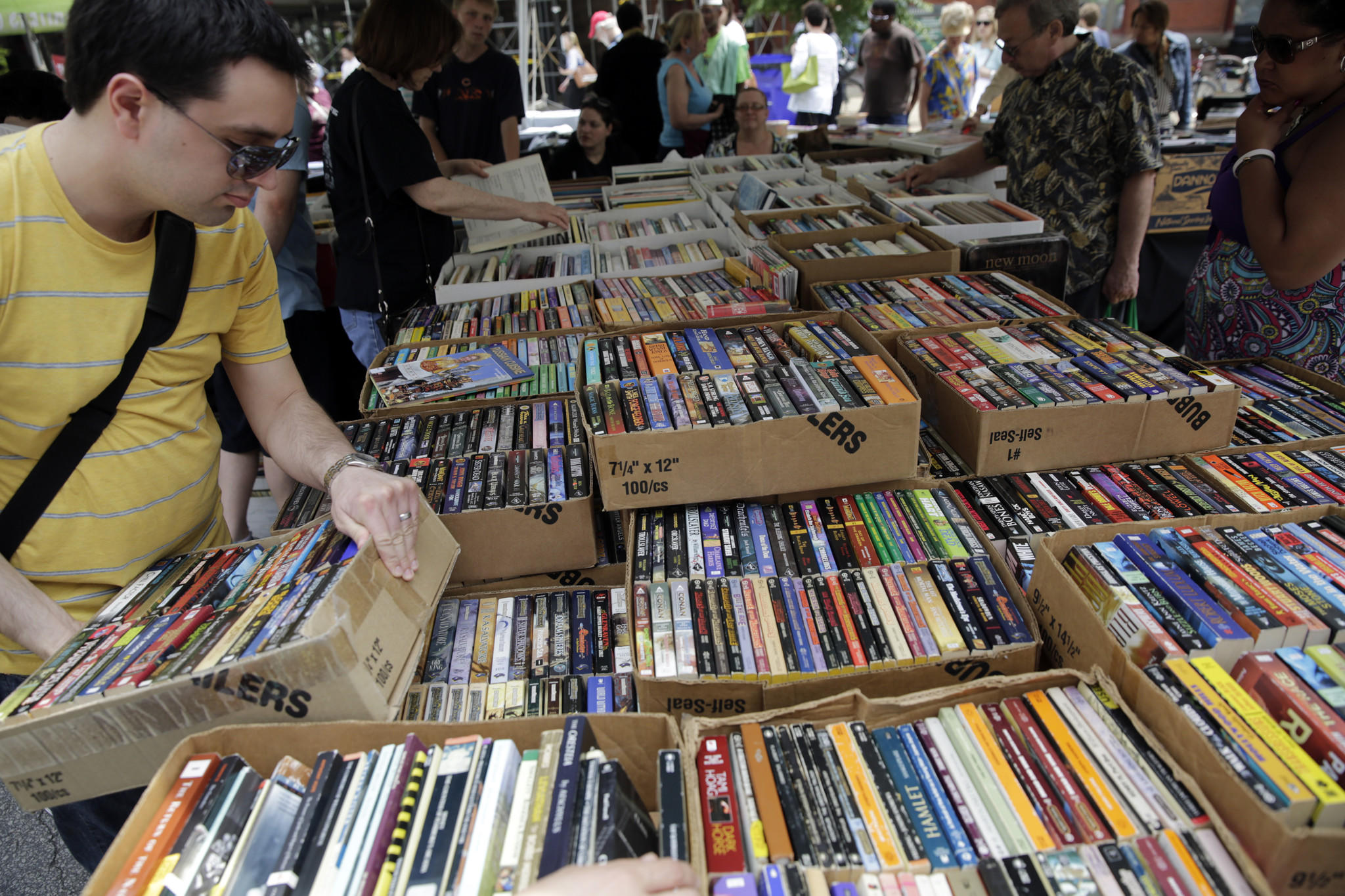 Shoppers look through paperbacks at the K&L Books booth at the 2013 Printers Row Lit Fest Sunday, June 9, 2013.