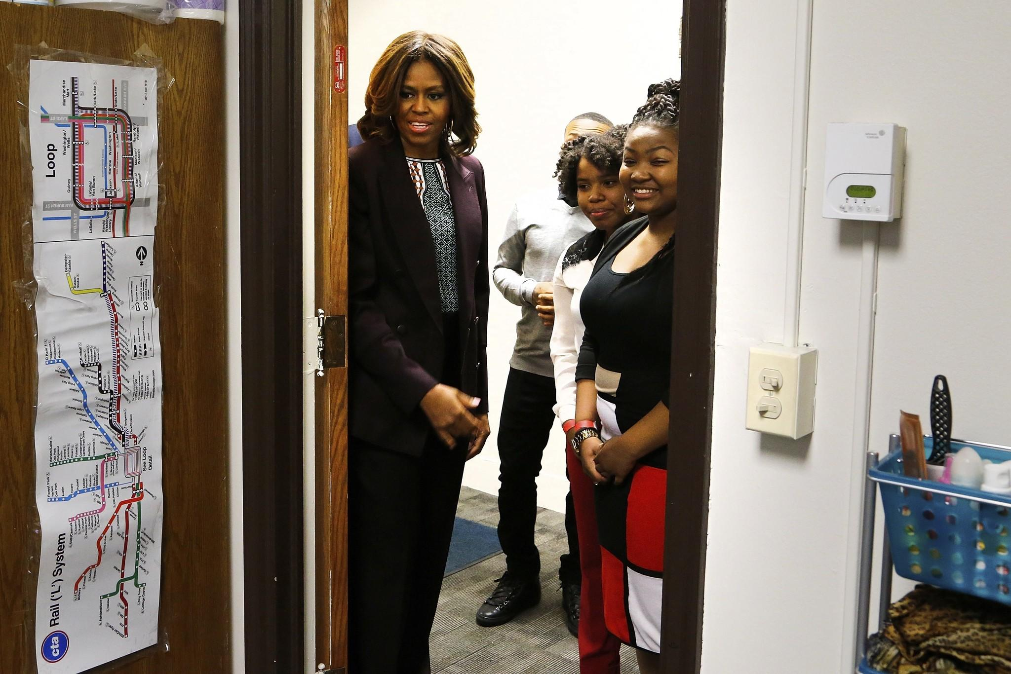 First lady Michelle Obama (left) looks into a dorm room during a campus tour of Howard University with high school students in Washington, D.C. Obama joined the juniors and seniors from Chicago public high schools on the first day of a four-day visit to Howard University called Escape to the Mecca.
