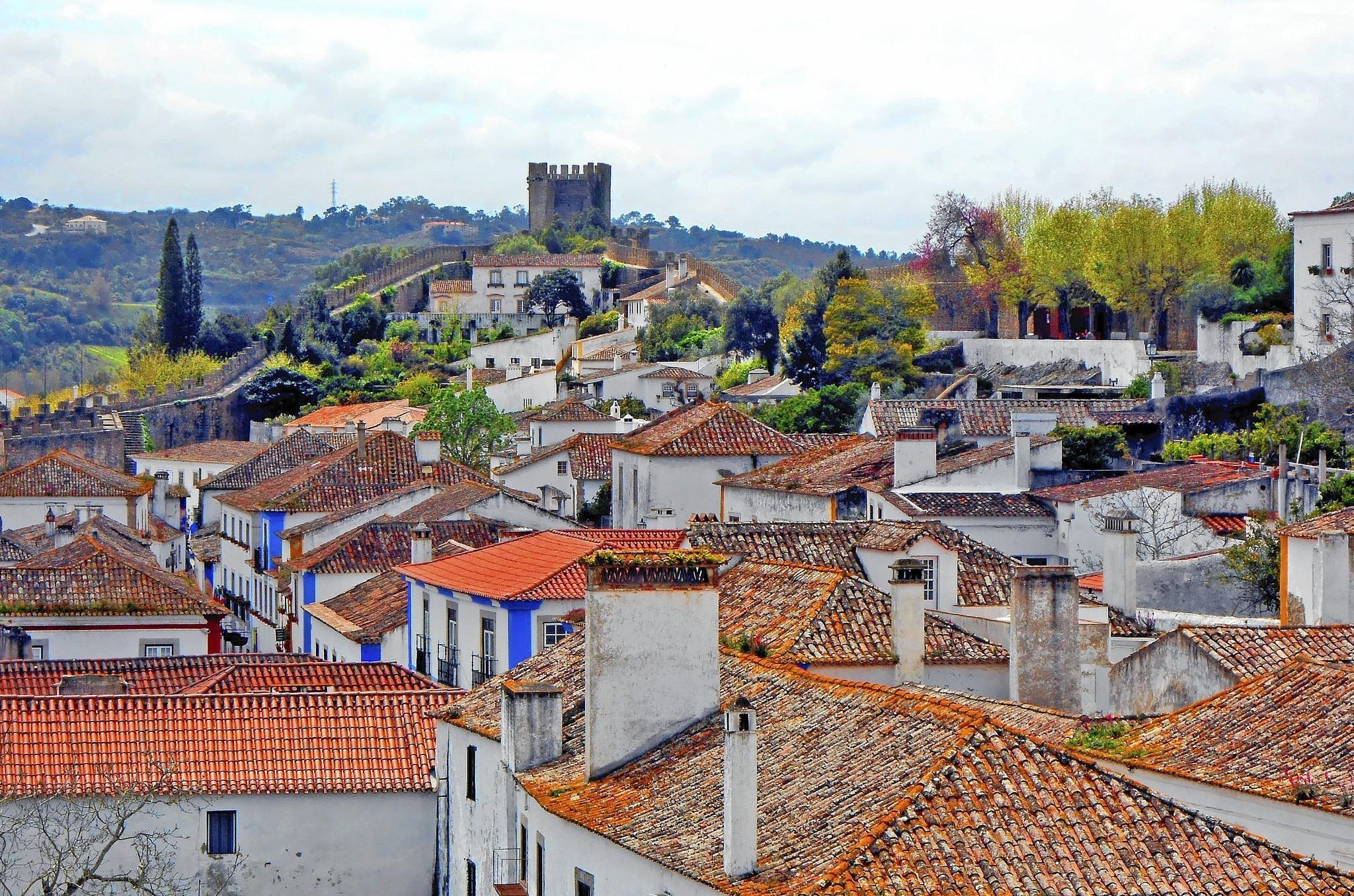 Looking out over the white washed, red-tiled homes and businesses of Obidos, a walled medieval village about an hour north of Lisbon, Portugal.