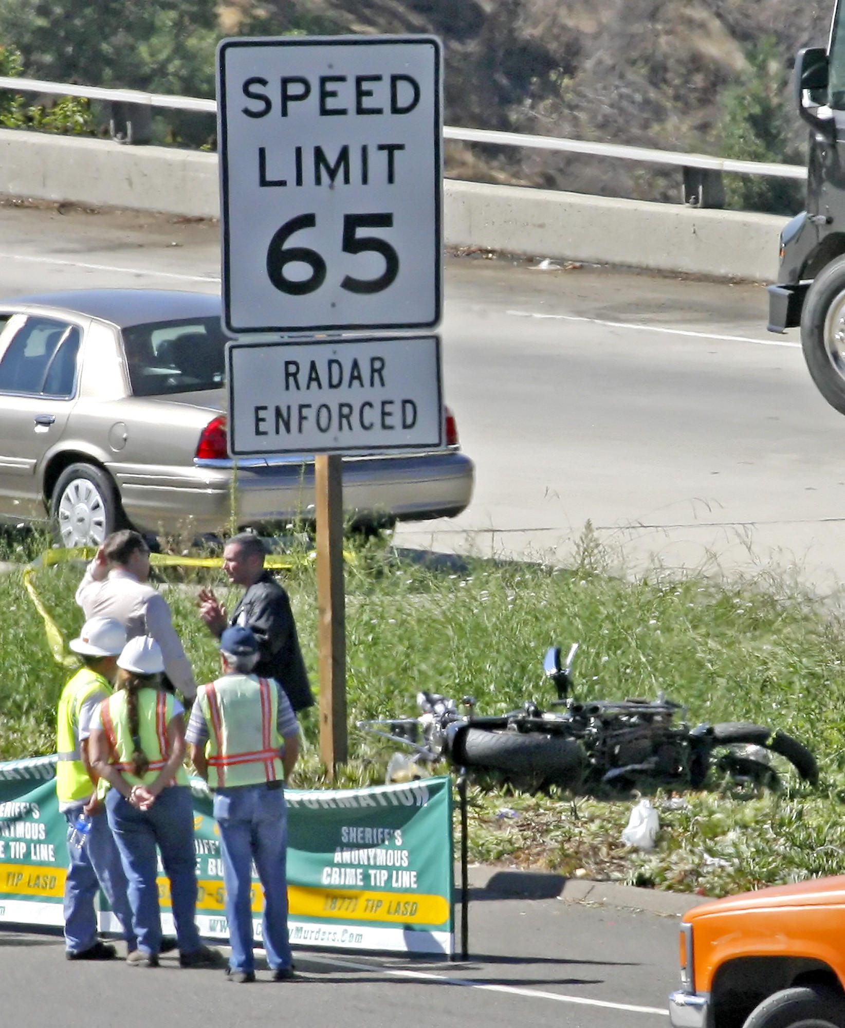 Emergency personnel talk near the wrecked motorcycle of man who was shot and killed early Wednesday morning, October 8, 2008. A reputed gang member accused of killing a Mongols Motorcycle Club member on the Glendale (2) Freeway in 2008 was sentenced on Wednesday, April 16, 2014, to life without the possibility of parole.