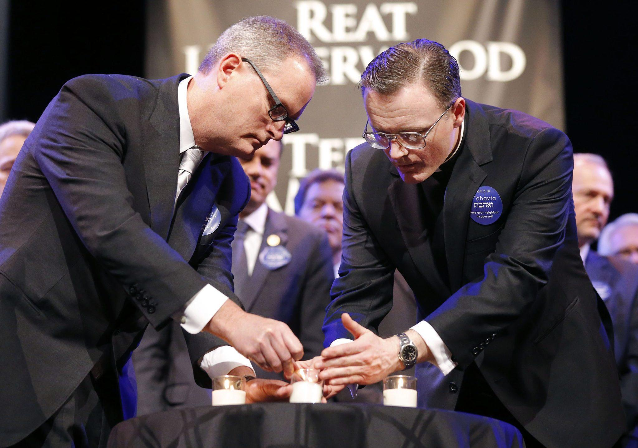 Rev. Adam Hamilton (L) and Fr. Stephen Cook light candles victims during the Interfaith Service of Unity and Hope to remember victims of Sunday's shootings at the Jewish Community Center in Overland Park, Kansas on April 17.