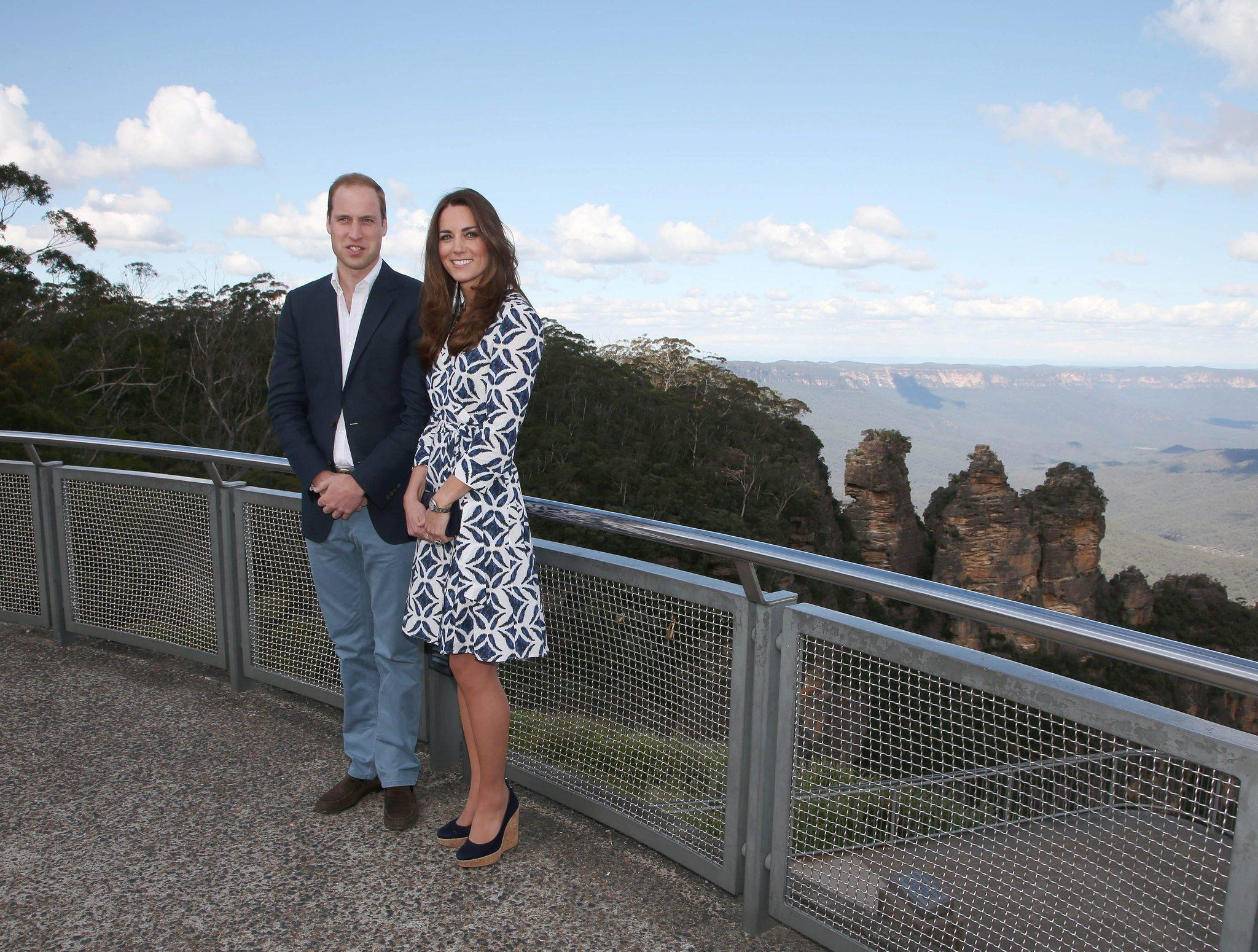 The Duke of Cambridge, Britain's Prince William, left, and his wife, the Duchess of Cambridge, dressed in Diane von Furstenberg, pose in front of the Three Sisters rock formation in the Blue Mountains during a tour of Echo Point in Katoomba.