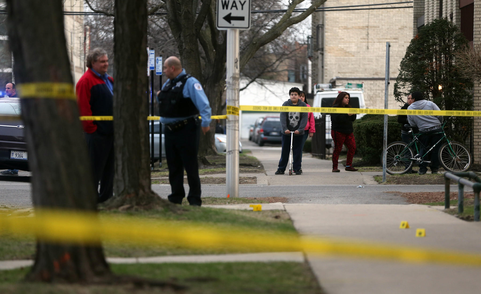 Neighbors watch as Chicago police respond to a shooting in the 5200 block of N. Rockwell Ave.