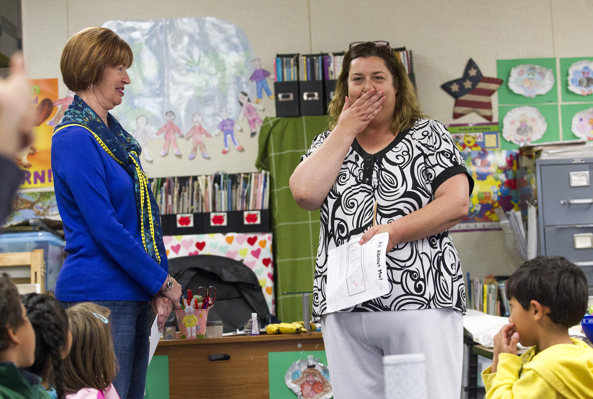 Cindy Fernald, right, a kindergarten teacher at College Park Elementary School, reacts after Barbara Steck, the president of the Costa Mesa Library Foundation, presents her with a nomination for the foundation's first ever Favorite Teacher contest on Thursday.