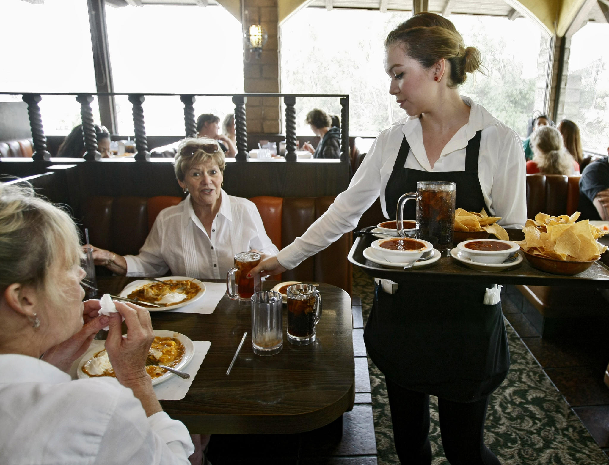 Ernie's Jr. Taco House waitress Tiffany Alvarado serves up lunch for Glendale residents Susan Schachtner, 56, left, and her mother Jackie Waldron, 80, right, at the Eagle Rock landmark restaurant on Thursday, April 17, 2014. Ernie's Jr. will close Saturday.