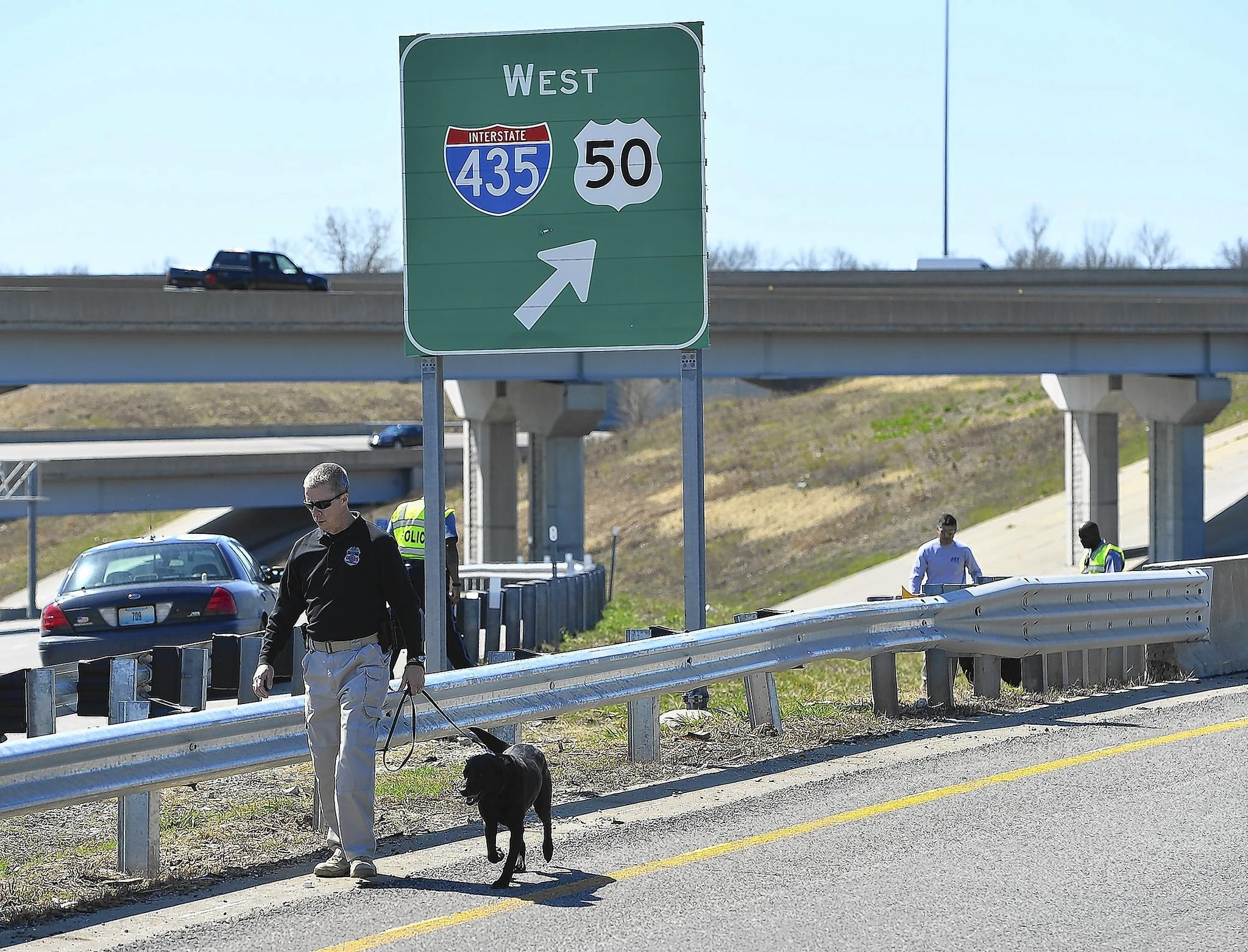 Kansas City police and federal agents investigate a shooting along southbound Interstate 435 in Kansas City, Mo. The gunman may be responsible for up to 20 shootings, authorities say.