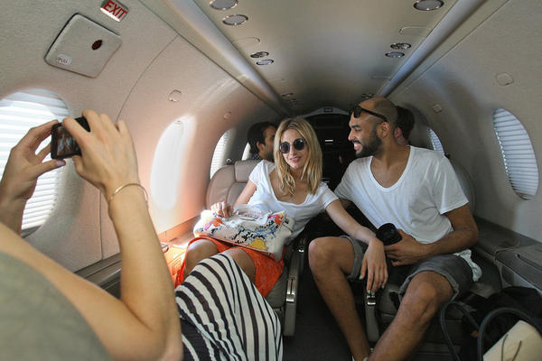 Izzy Lawrence, far left, photographs Sophie Ball, middle, and Tom Hardy, right, aboard Surf Air's Pilatus PC-12 in Burbank