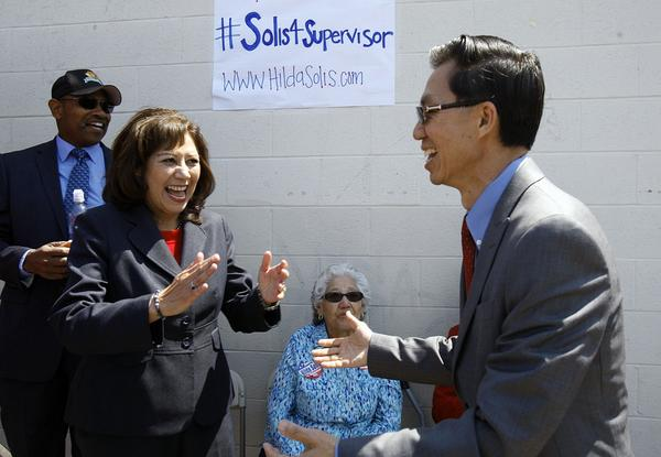 "At a debate Thursday, supervisorial candidates Juventino ""J"" Gomez and  April Saucedo Hood noted the absence of opponent Hilda Solis, whose campaign for a seat on the Los Angeles County Board of Supervisors is leading in fundraising."