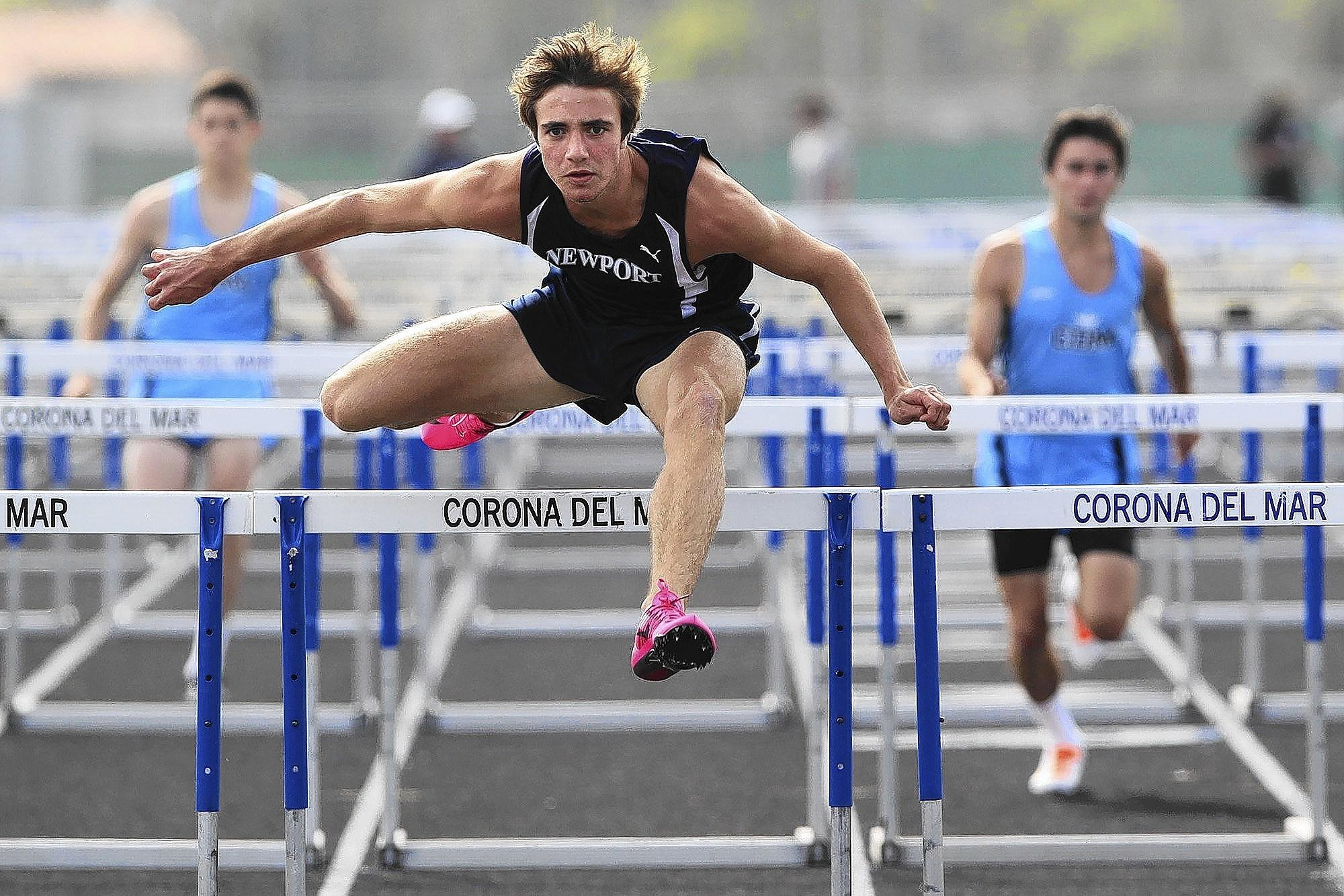 Newport Harbor High senior Marcell DeBarros finishes first in the boys' 110 meter high hurdles during the Battle of the Bay track and field meet on Thursday.