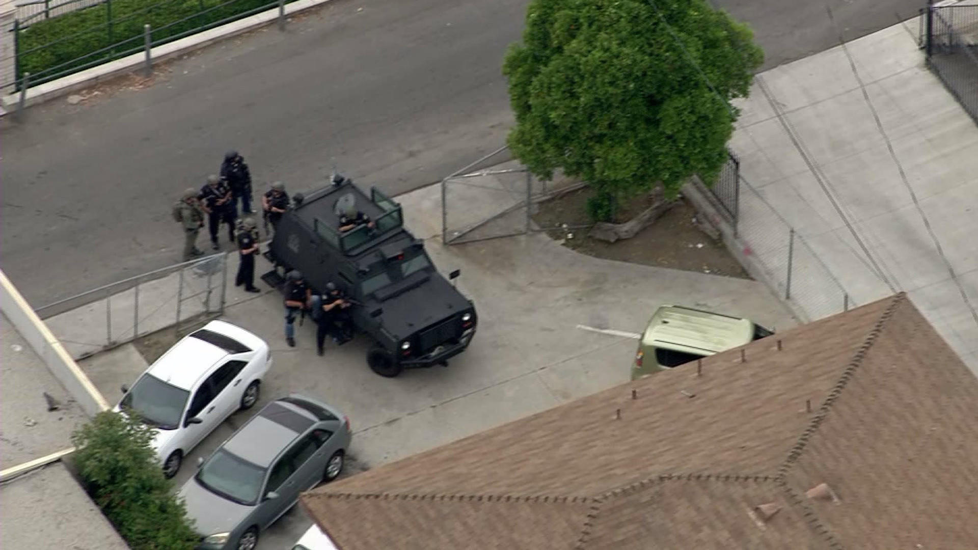 Authorities take a position outside a Whittier apartment complex during a standoff with a man believed to have taken a hostage.
