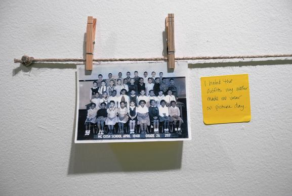 A note written by a visitor hangs next to a grade school picture at a Samantha Hill exhibit at the Hyde Park Arts Center.