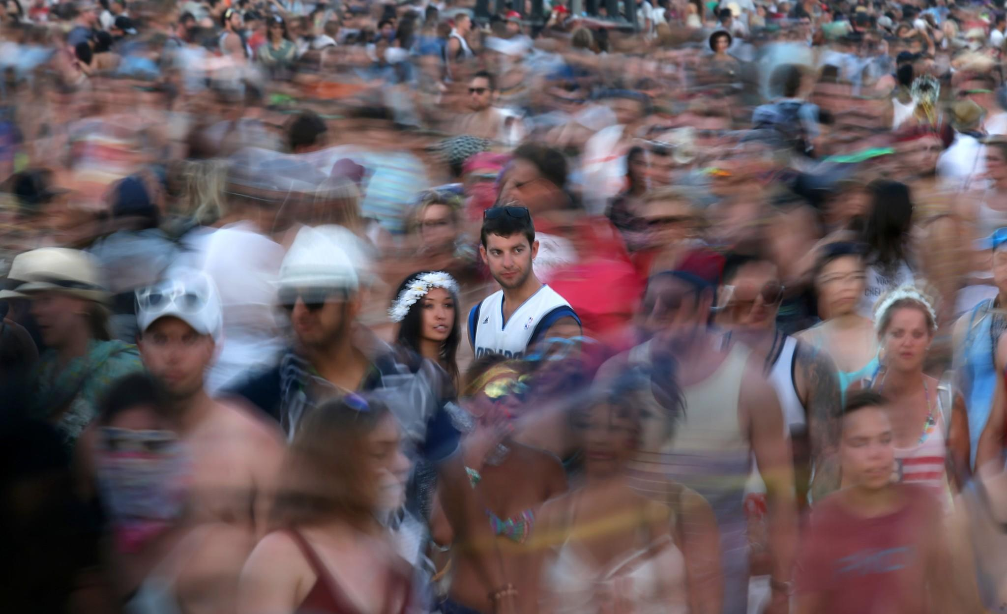 Shara Soo, 27, left, and friend Tyler Kiefer, 23, of San Francisco, stand in a sea of moving people on the first weekend of the 2014 Coachella Music and Arts Festival.