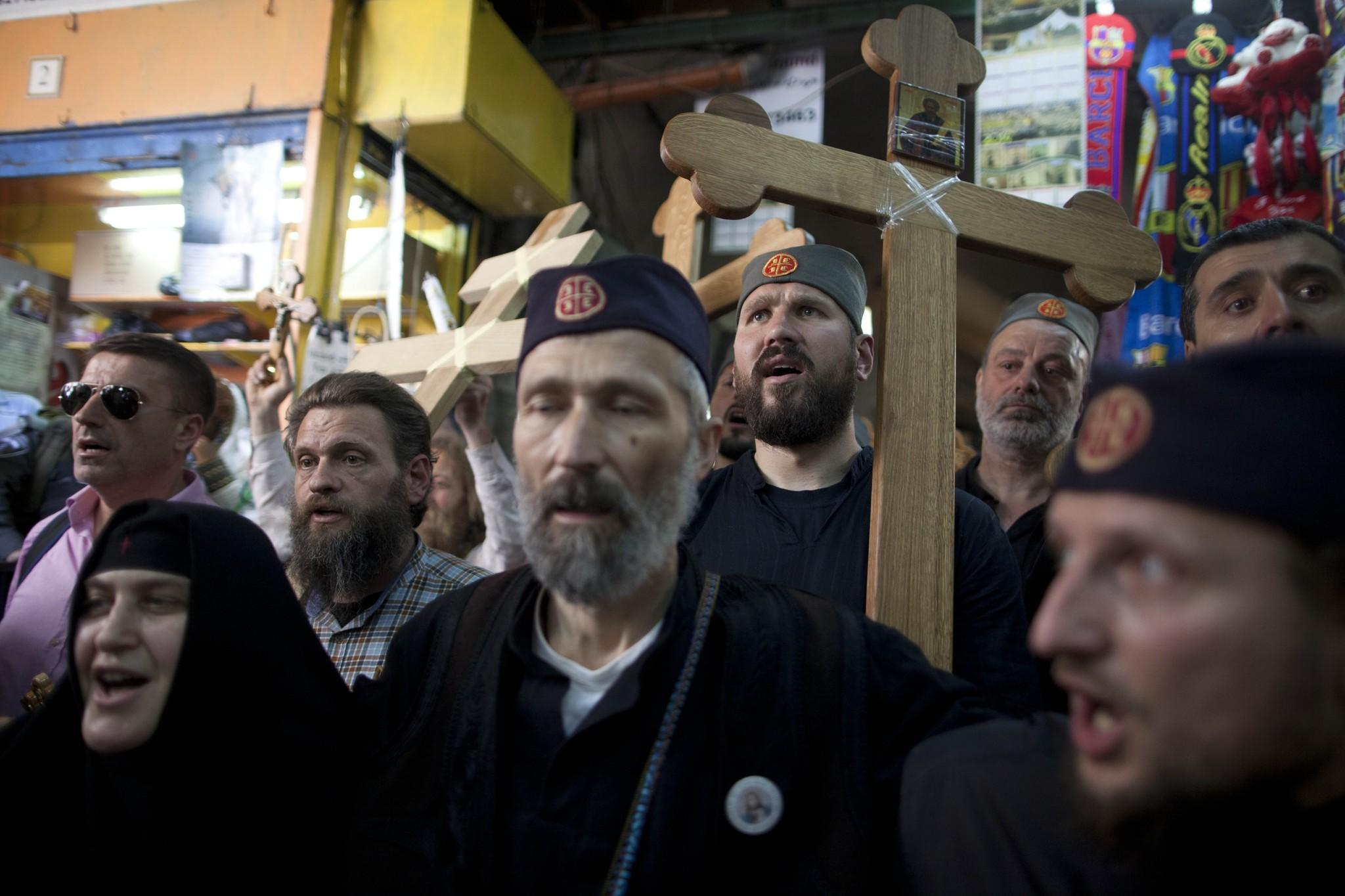 Orthodox Christian pilgrims hold wooden crosses as they take part in the Good Friday procession along the Via Dolorosa in Jerusalem's Old City on Friday.
