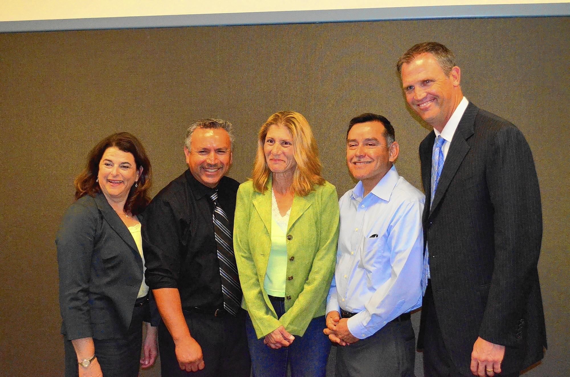 Orange County Board of Education Trustee Elizabeth Parker, left, and John Drake, the Director of Certificated Personnel, right, celebrate Newport-Mesa employees Jose Bedolla, Roberta Geller, Alejo Ortiz being named Classified Employees of the Year during a board meeting Wednesday.