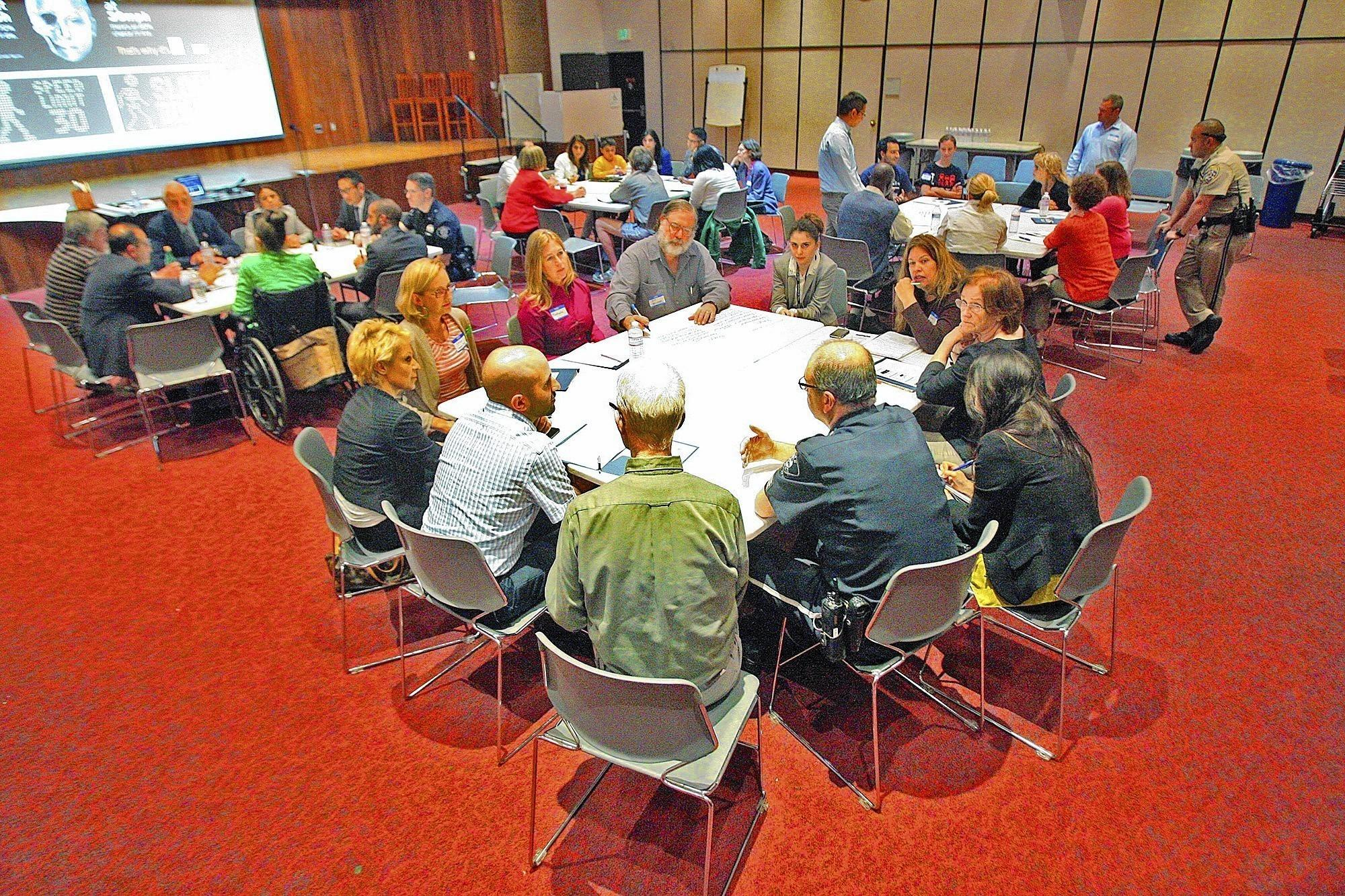 Several tables of community members gather to discuss ideas for pedestrian safety at a community pedestrian safety training at the Glendale Central Library on Thursday, April 17, 2014. The program works with the public to come up with answers to improve safety in Glendale.