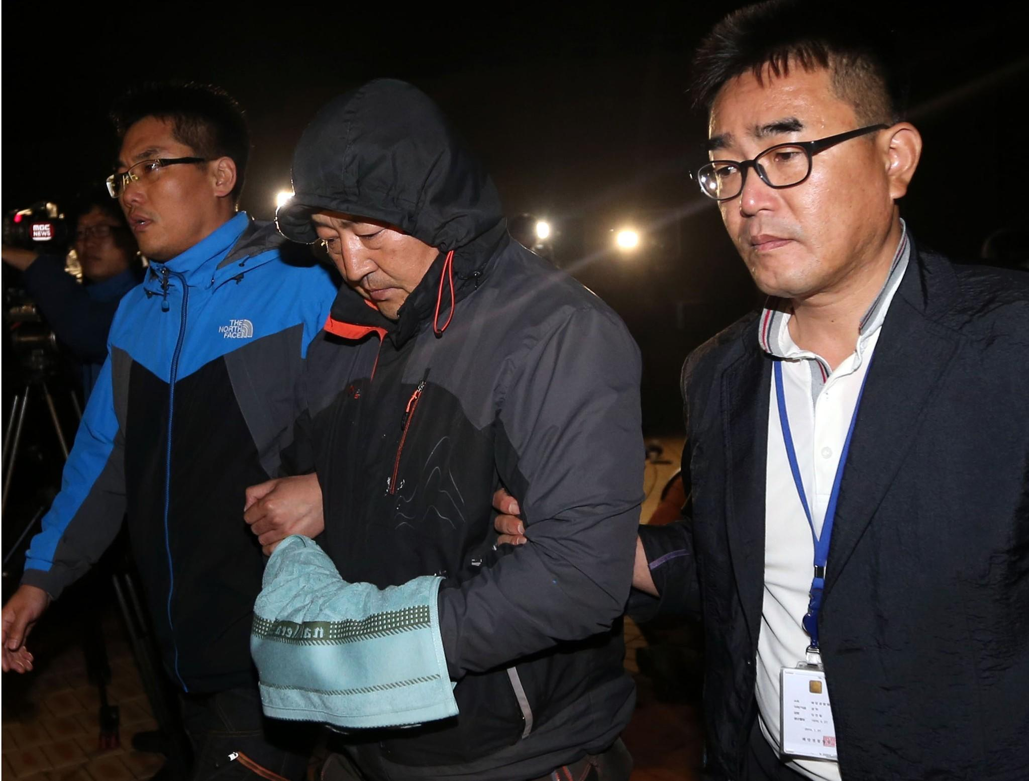 Lee Joon-seok, center, the captain of the sunken ferry Sewol, leaves a court that issued a warrant for his arrest.