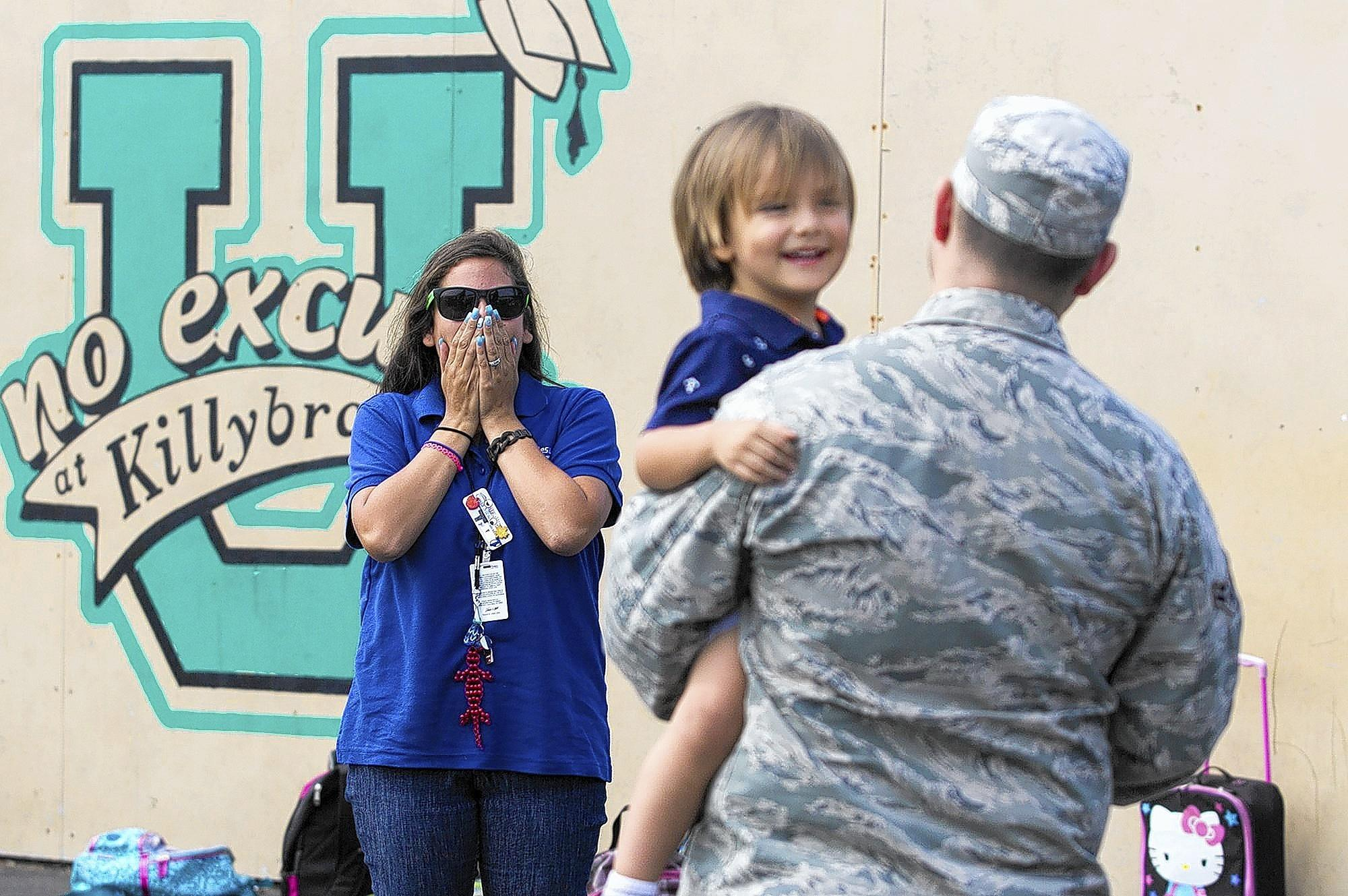 Theresa Byrne is surprised by her husband, Airman 1st Class Zachary Byrne, with the 30th Security Forces Squadron, and their son, Dominic, at Killybrooke Elementary School where she works as a site supervisor for the Recreation On Campus for Kids after school program on Thursday.