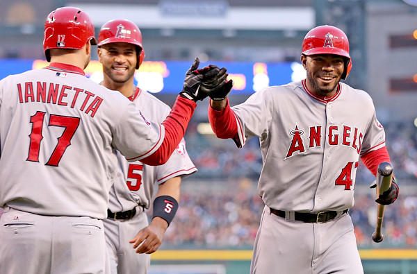 Angels second baseman Howie Kendrick is congratulated by teammate Chris Iannetta after hitting a two-run home run against the Tigers that drove in Albert Pujols (5) in the third inning Friday night in Detroit.