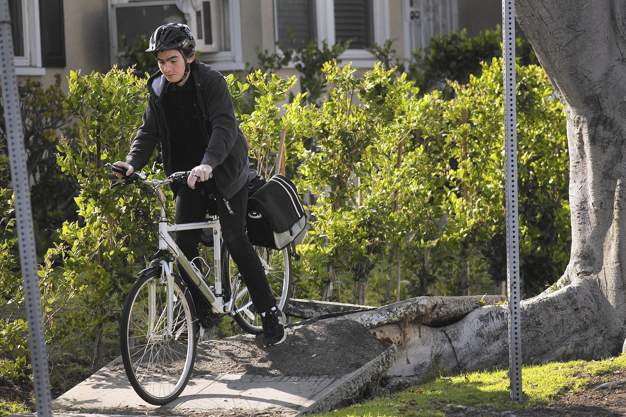 """Ethan Robarts, 17, navigates the sidewalk along the 2400 block of Prosser Avenue in Los Angeles. """"I just jump over it,"""" Robarts said."""