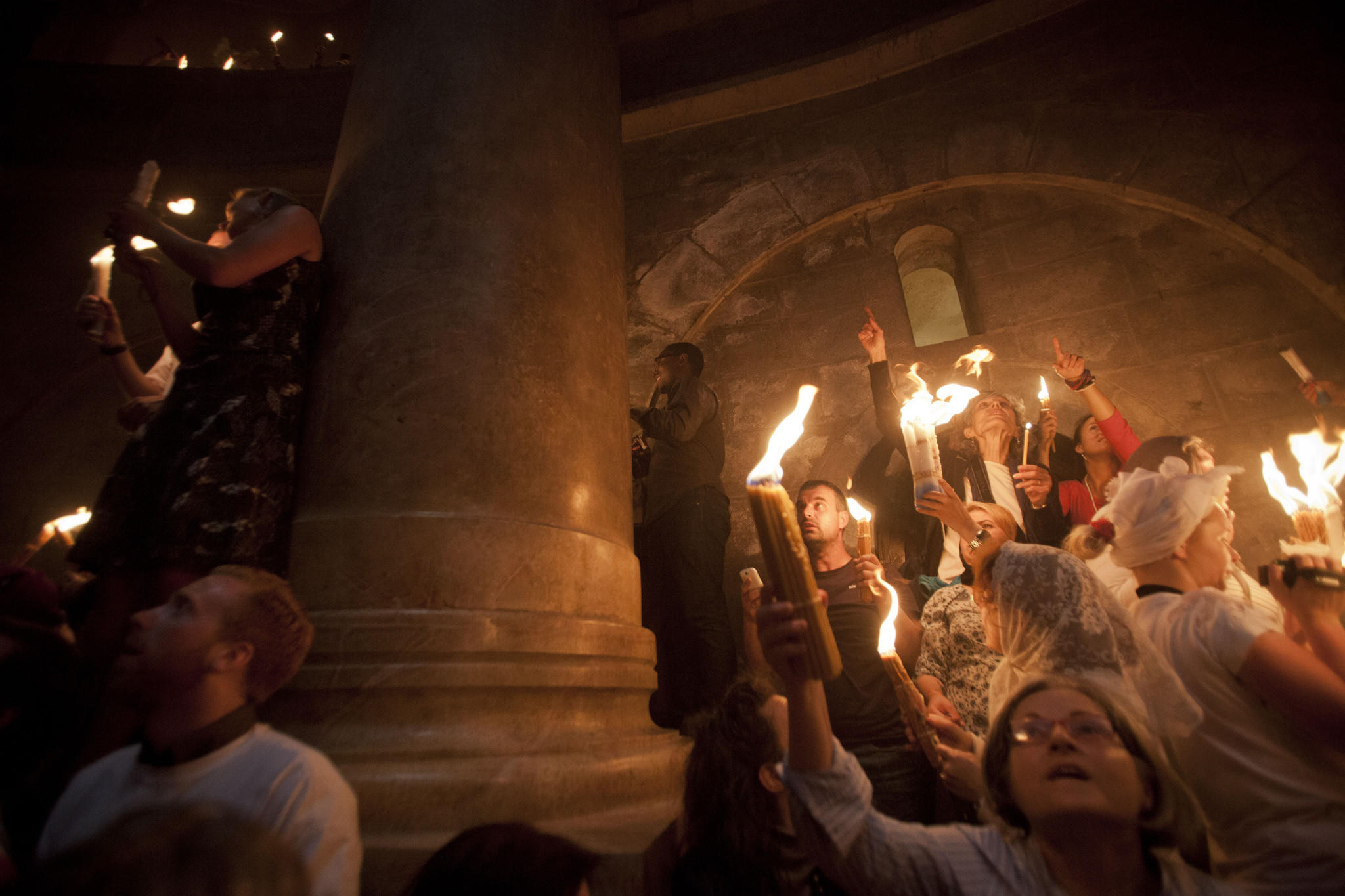 """Christian pilgrims hold candles at the Church of the Holy Sepulcher, believed to be the burial site of Jesus Christ, during the ceremony of the """"holy fire"""" in Jerusalem's Old City on Saturday."""
