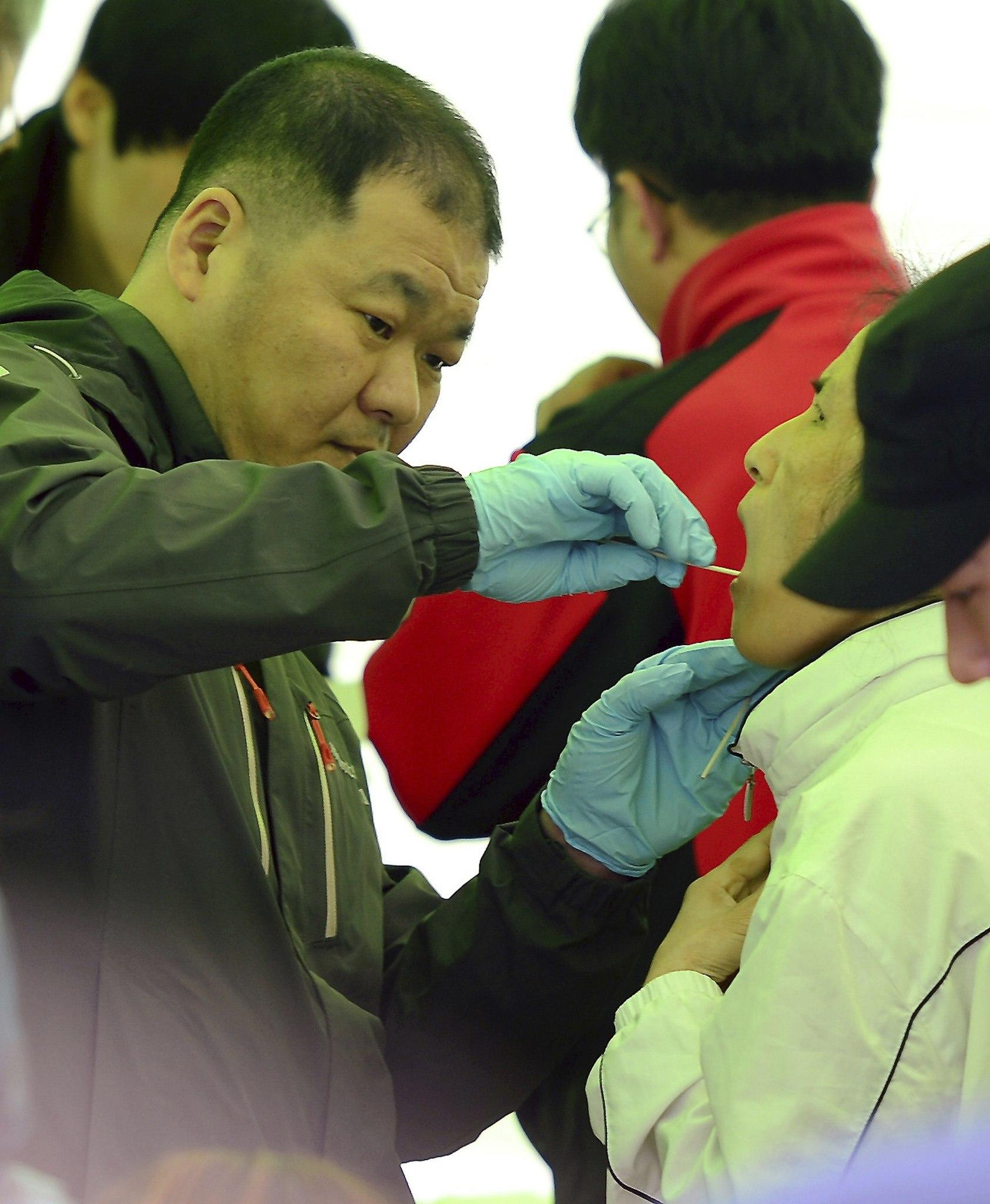 An official uses a swab to collect a DNA sample from a family member of a missing passenger onboard the sunken South Korean ferry Sewol, in Jindo April 19, 2014.