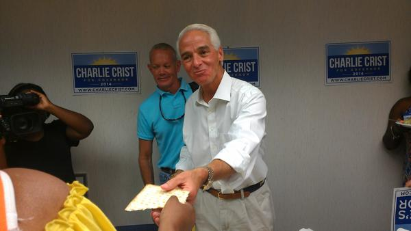 Charlie Crist offers matzo to a supporter at the opening of his campaign office in Plantation on April 19, 2014. (Photo by Anthony Man)