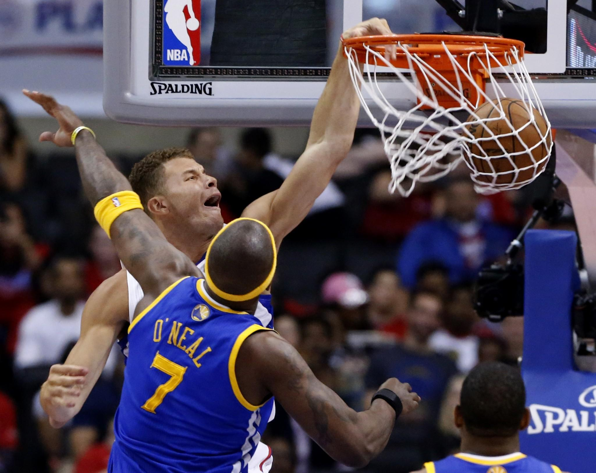 Clippers power forward Blake Griffin slams the ball past Warriors center Jermaine O'Neal in the second half Saturday afternoon during Game 1 at Staples Center.