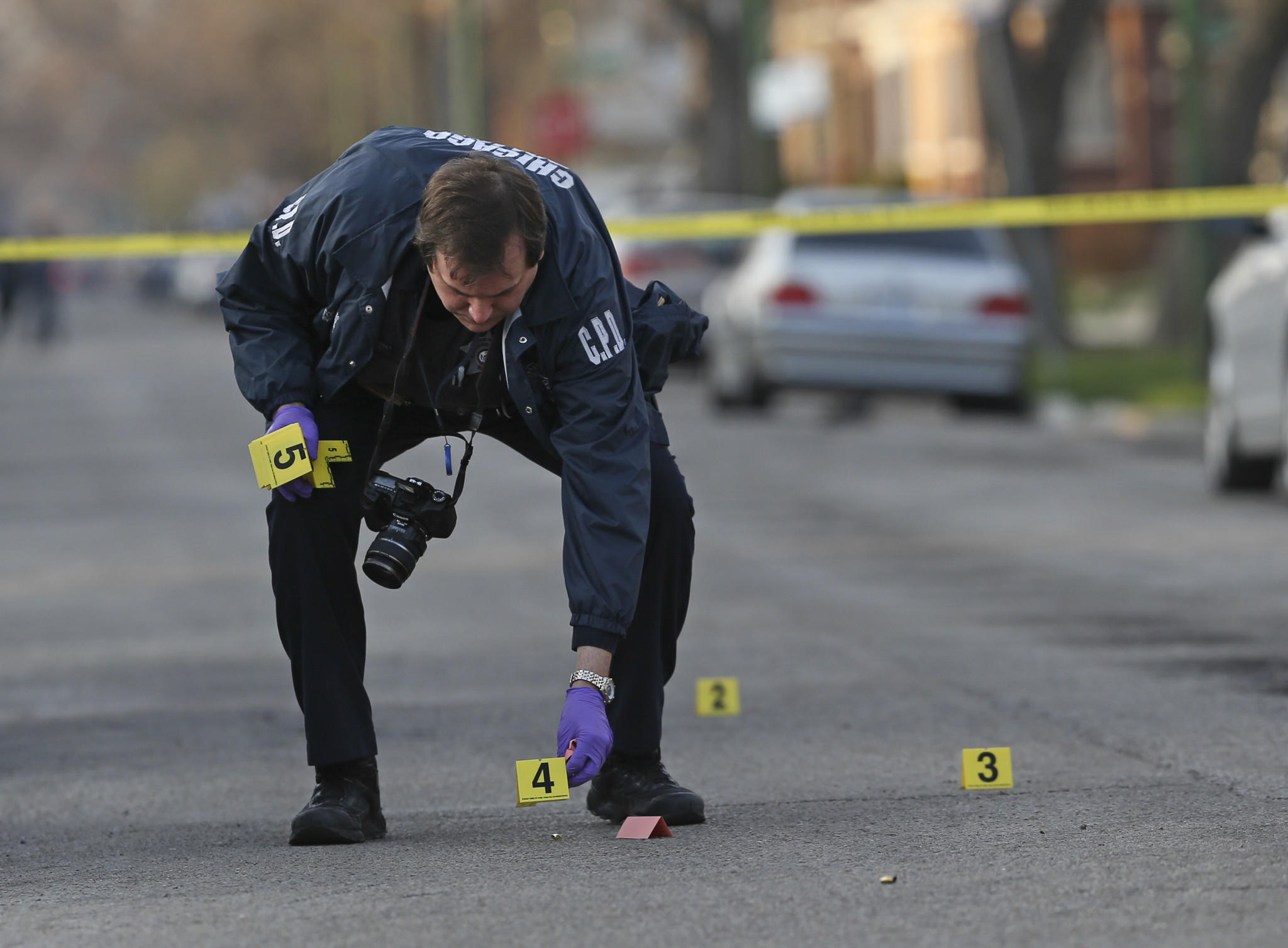 A Chicago police department evidence technician marks spent bullet casings while investigating the scene of a shooting at 85th Street and Hermitage Avenue, in Chicago.