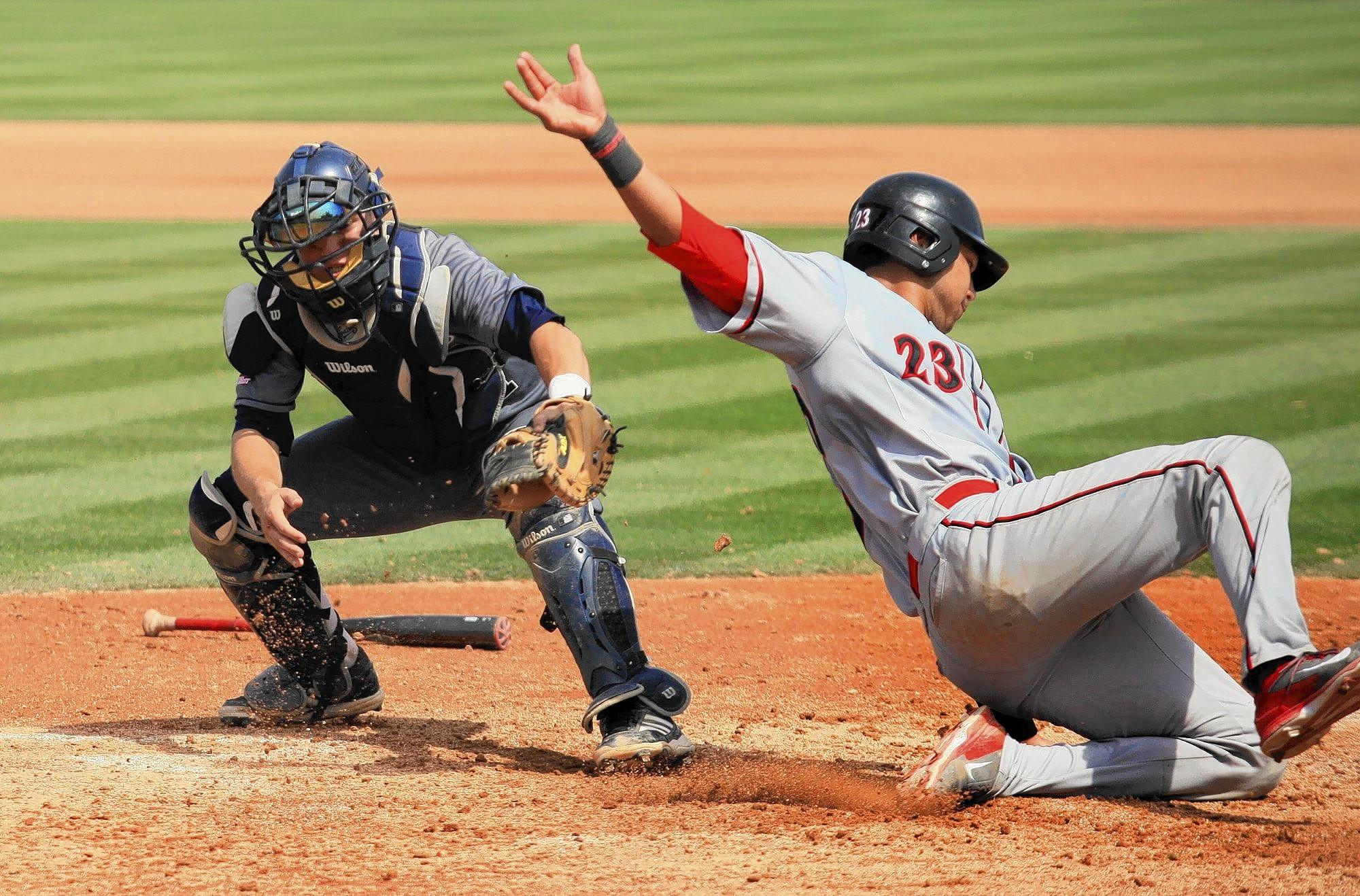 UC Irvine catcher Jerry McClanahan, left, is short of a tag on San Diego State's Brad Haynal at home plate during the seventh inning in a nonconference game at Anteater Ballpark on Saturday. The Anteaters lost 4-3.