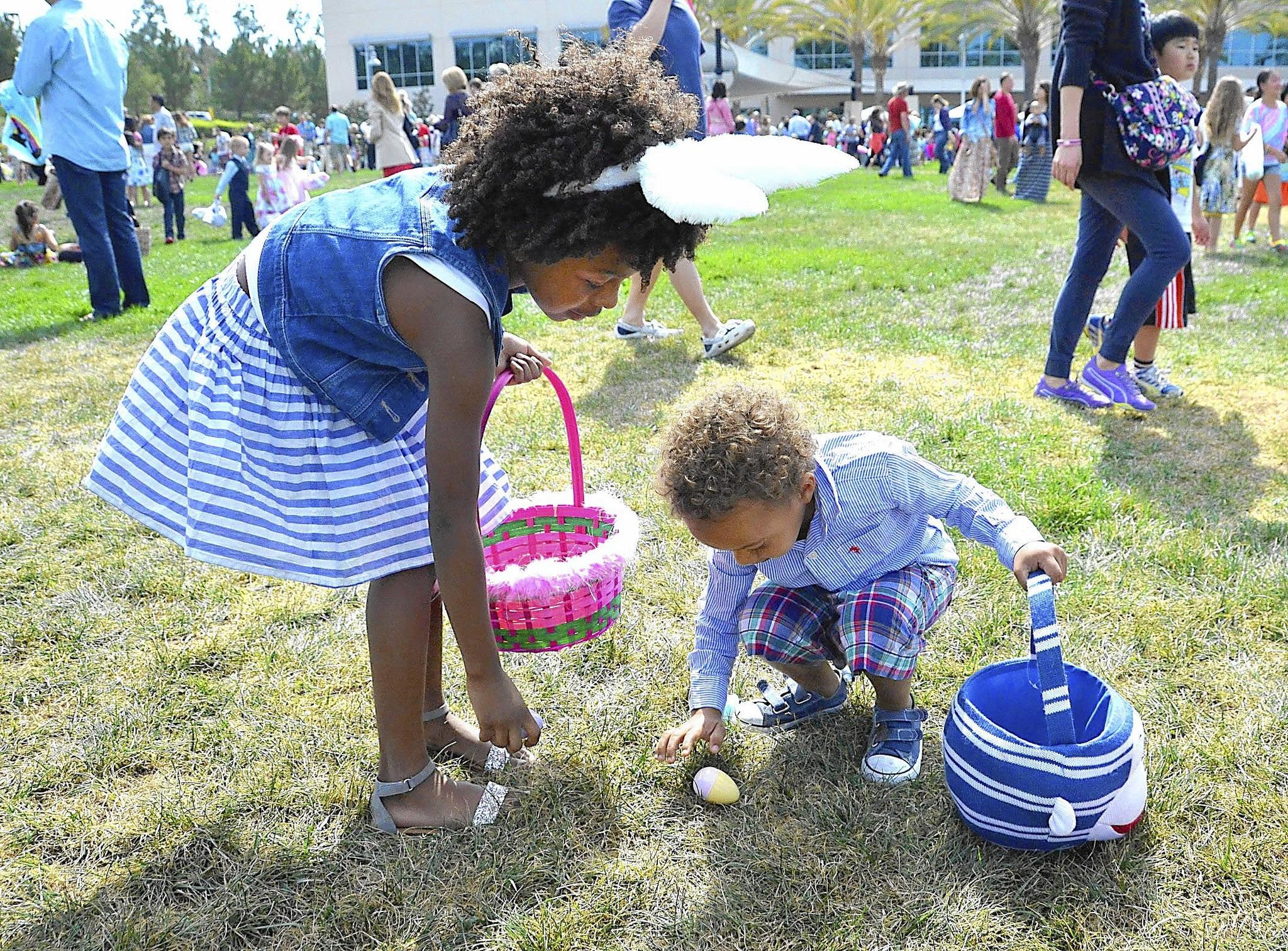 Leah Browne helps Knox De Allen gather candy filled eggs during the annual easter egg hunt at Mariners Church on Saturday.