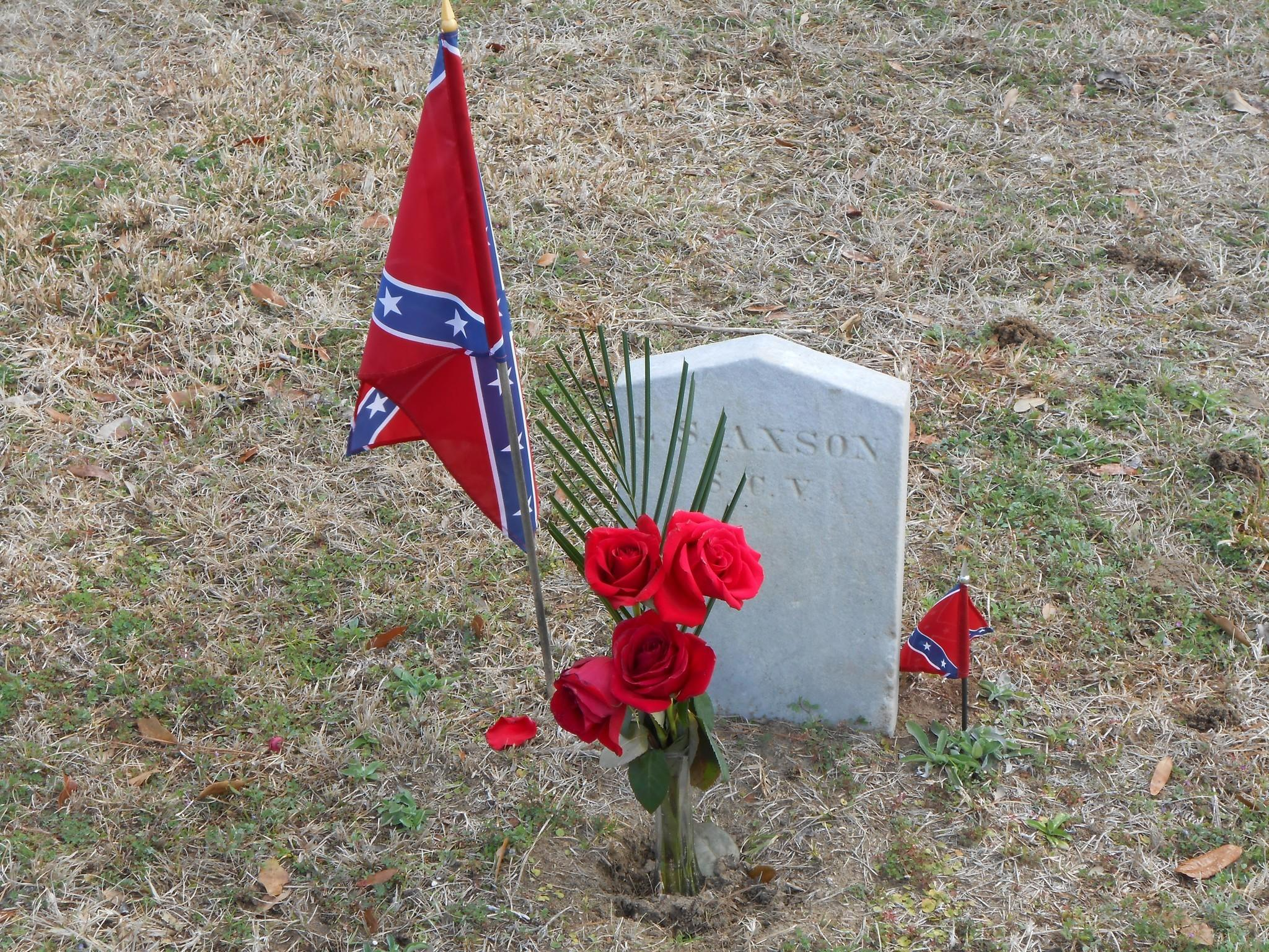 Flowers and miniature confederate flags are seen alongside a gravestone in Charleston's Magnolia Cemetery.