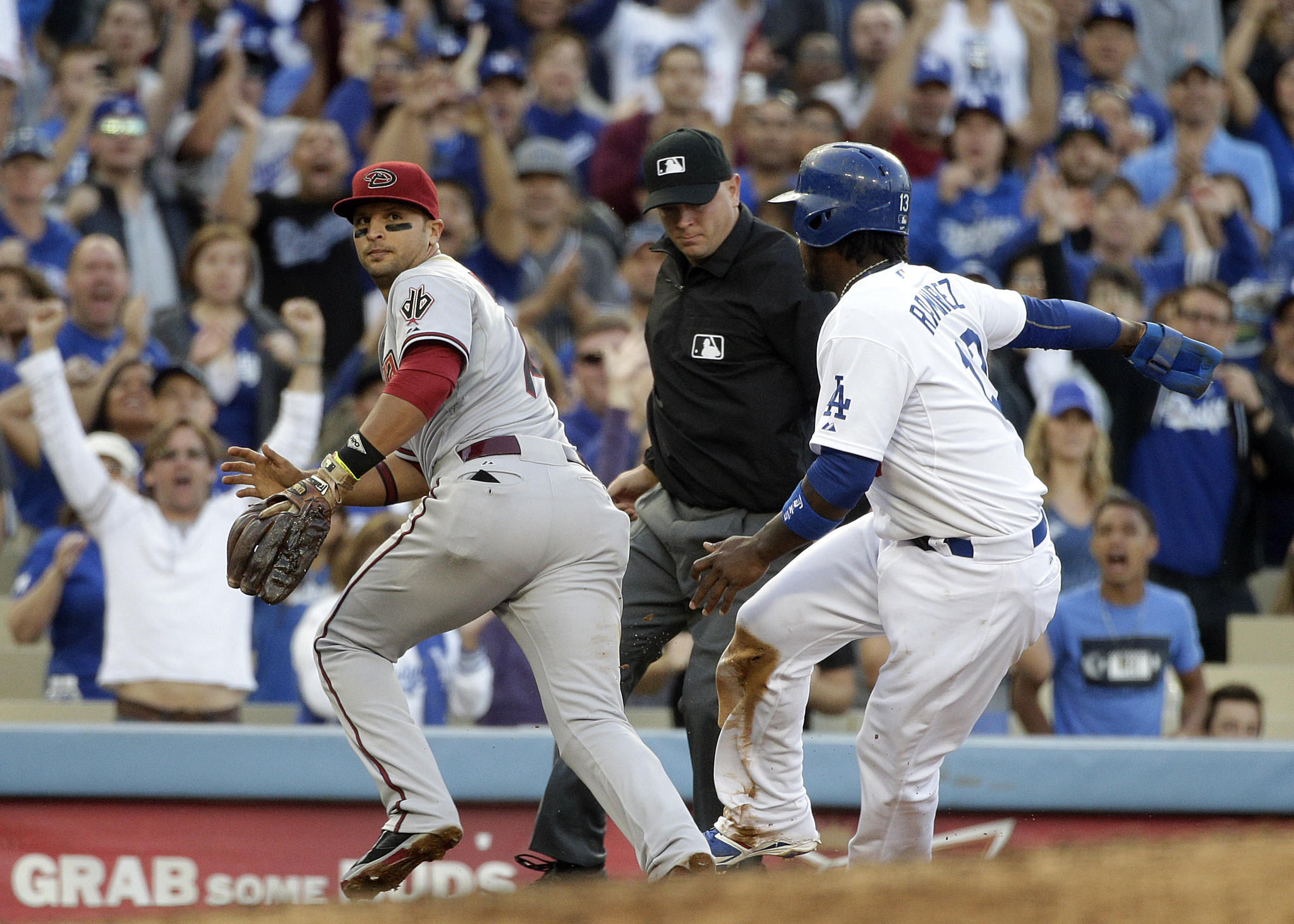 Hanley Ramirez, right, safely takes third base as Arizona's Martin Prado goes after the ball during the fifth inning of the Dodgers' 8-6 victory Saturday at Dodger Stadium.
