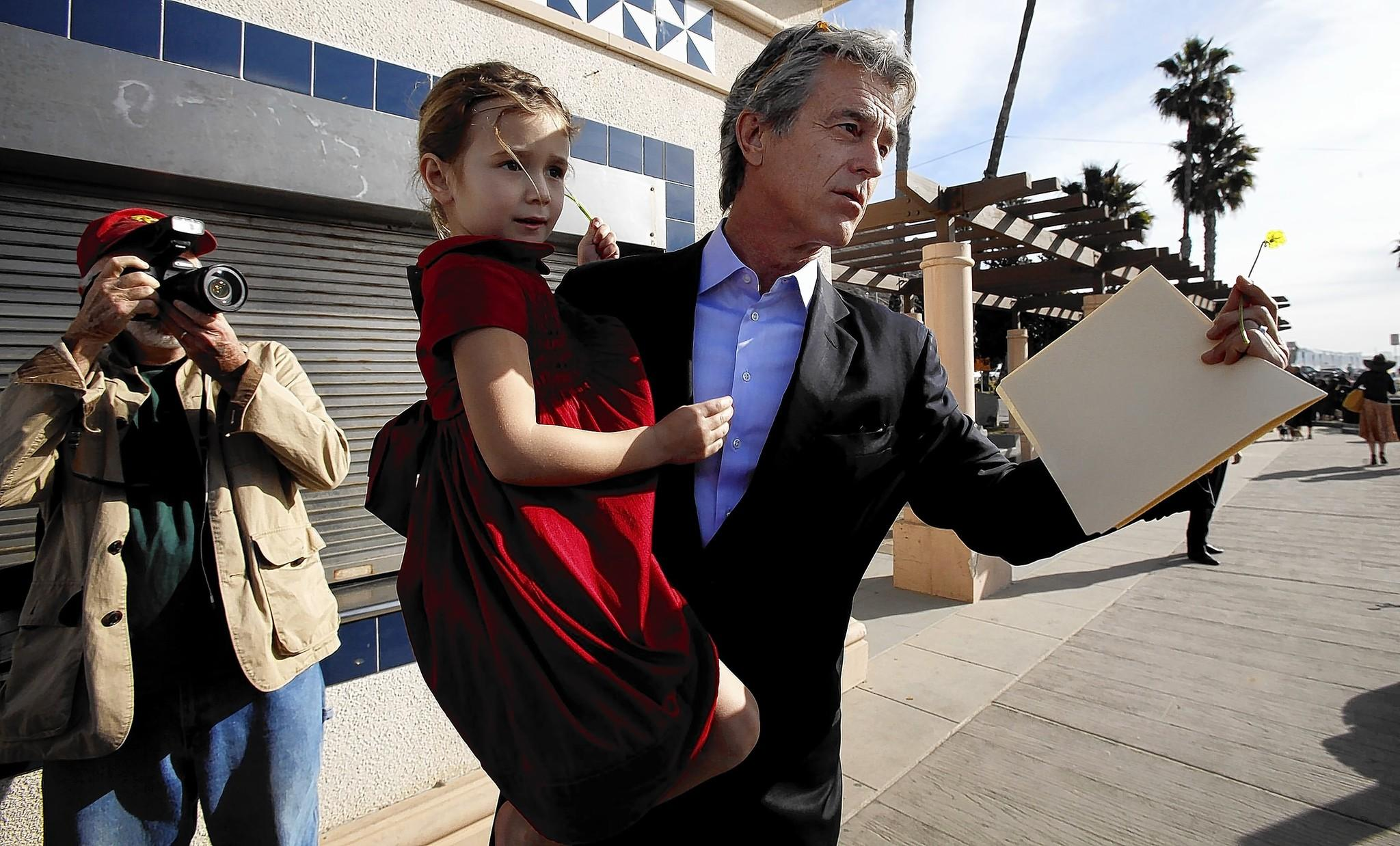 Bobby Shriver, seen here earlier this year holding his daughter, has decried the voluntary spending limit on candidates running for the Los Angeles County Board of Supervisors.