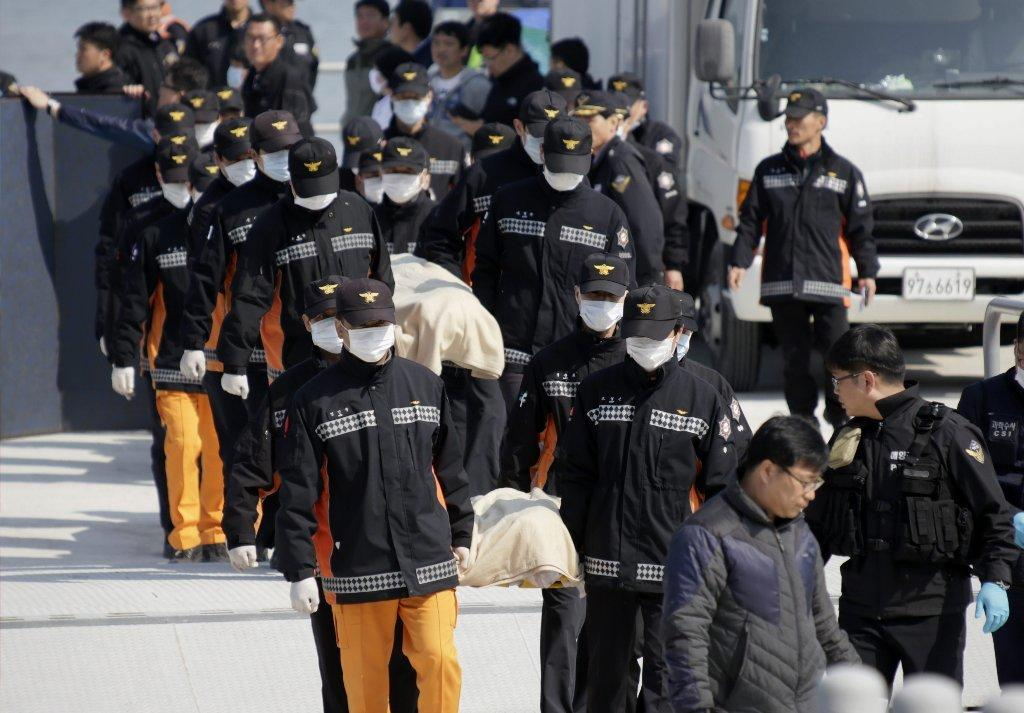 Rescuers carry bodies retrieved from the sunken ferry Sewol at the port of Jindo, South Korea.